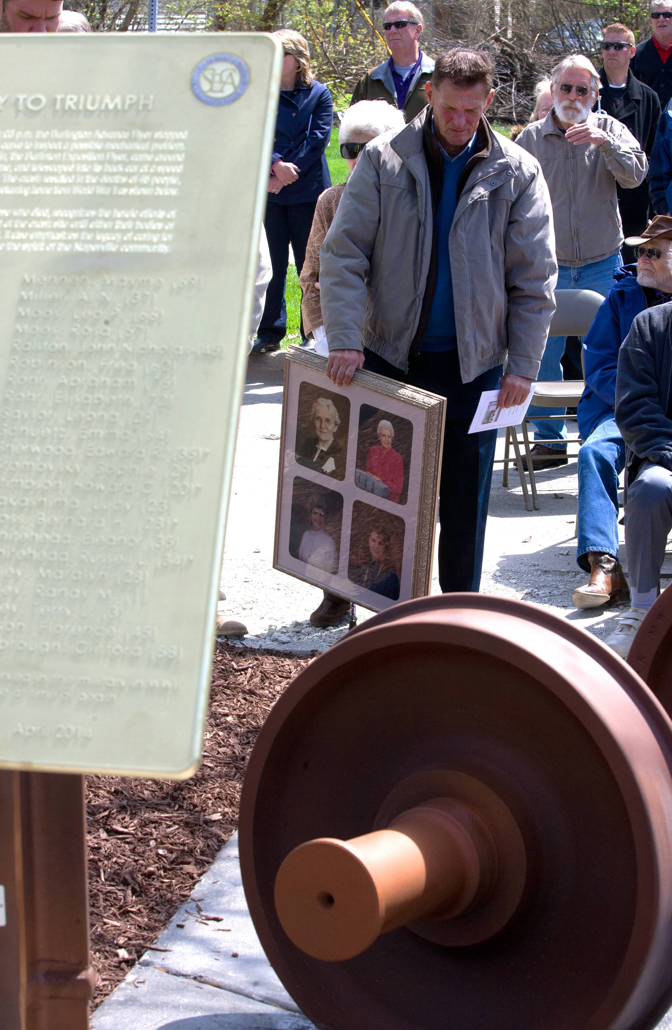 Paul McClelland of South Barrington holds framed photos which include one of his grandmother, Emma Scheutz, who was killed at the Loomis Street crossing. A new Naperville sculpture is dedicated the 1946 train crash.