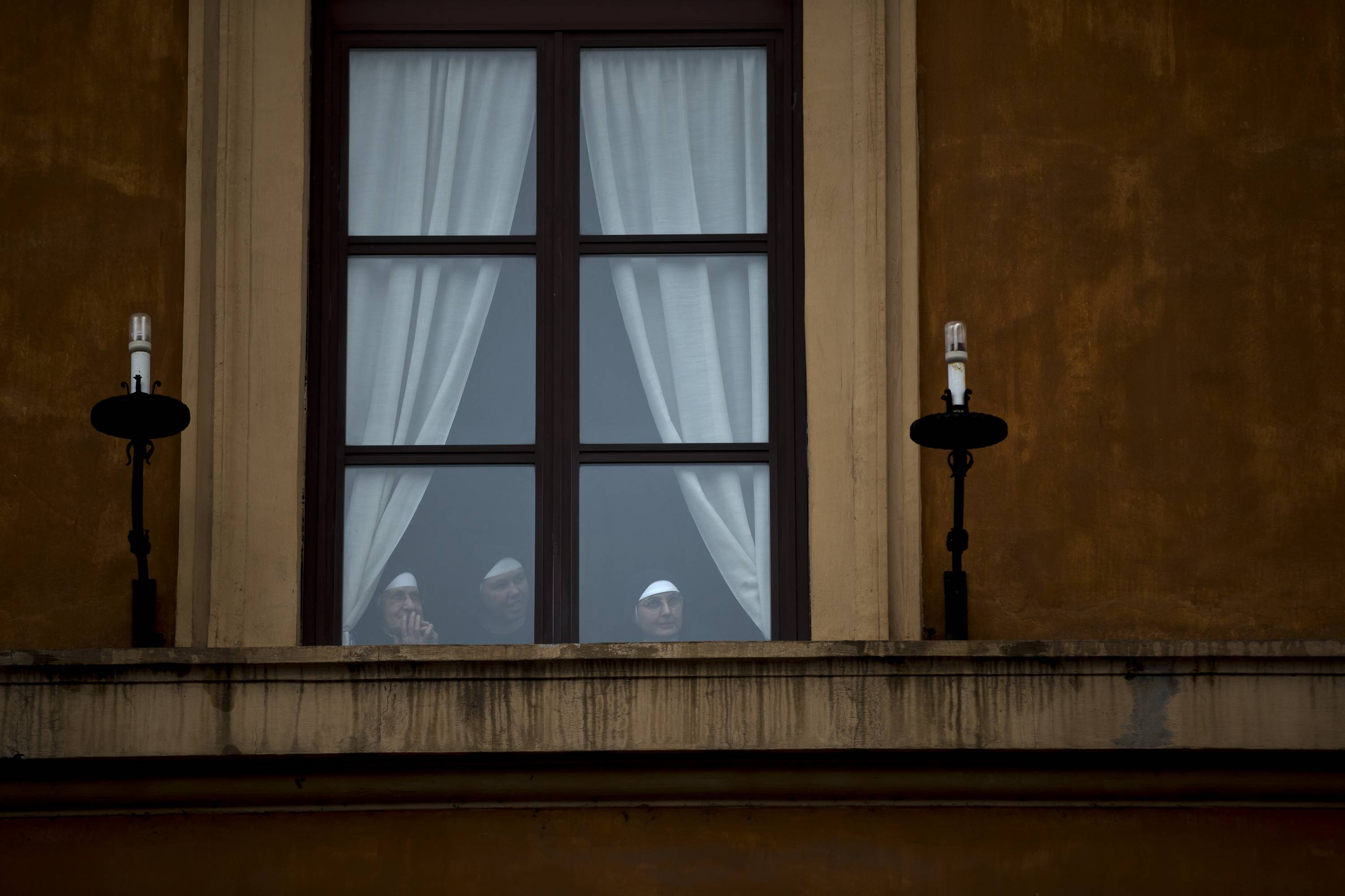 Nuns watch pilgrims from a window outside St. Peter's Square at the Vatican, Saturday.
