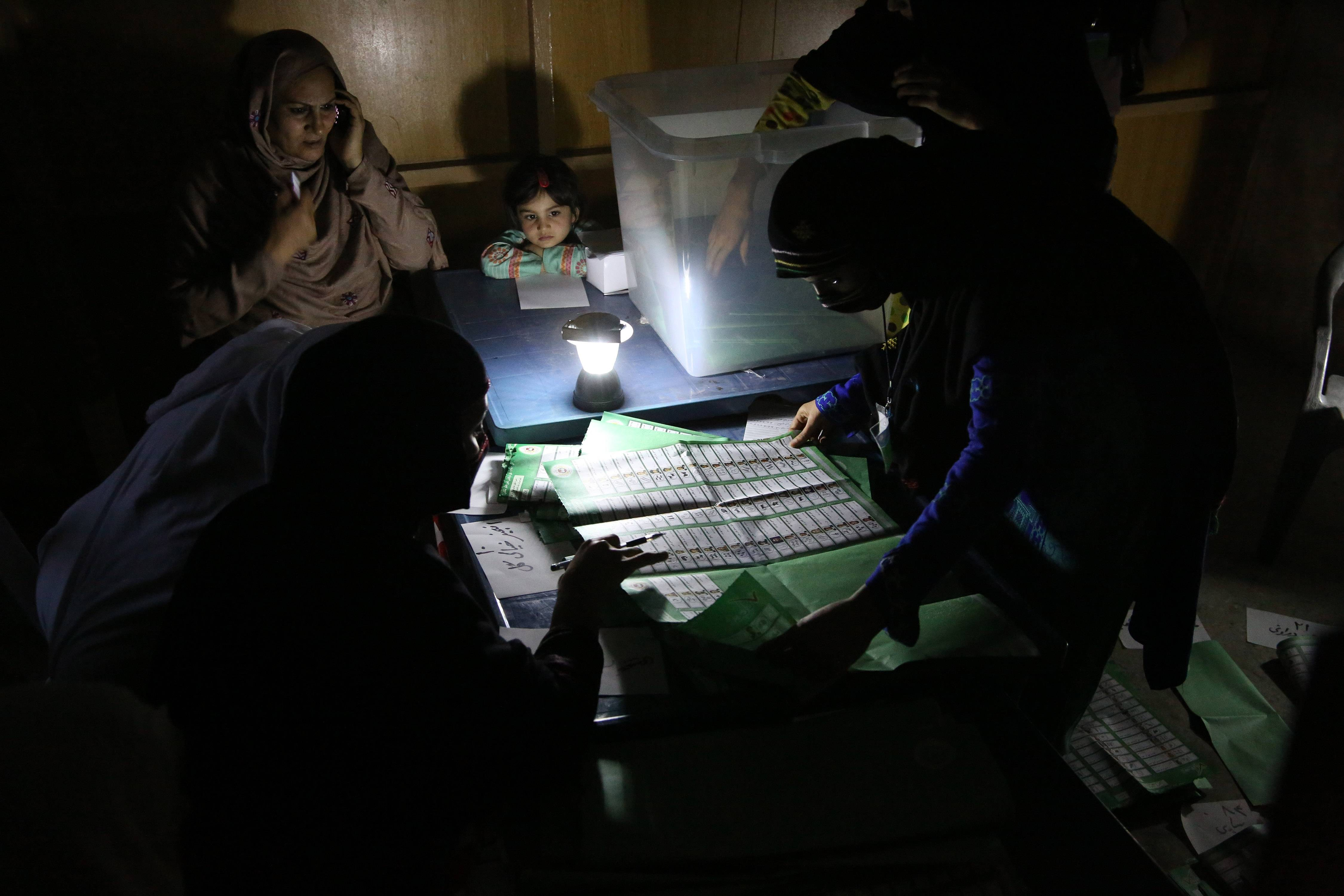 Afghan election workers on April 5 count ballots by the light of a lantern at a polling station in Jalalabad, east of Kabul, Afghanistan.