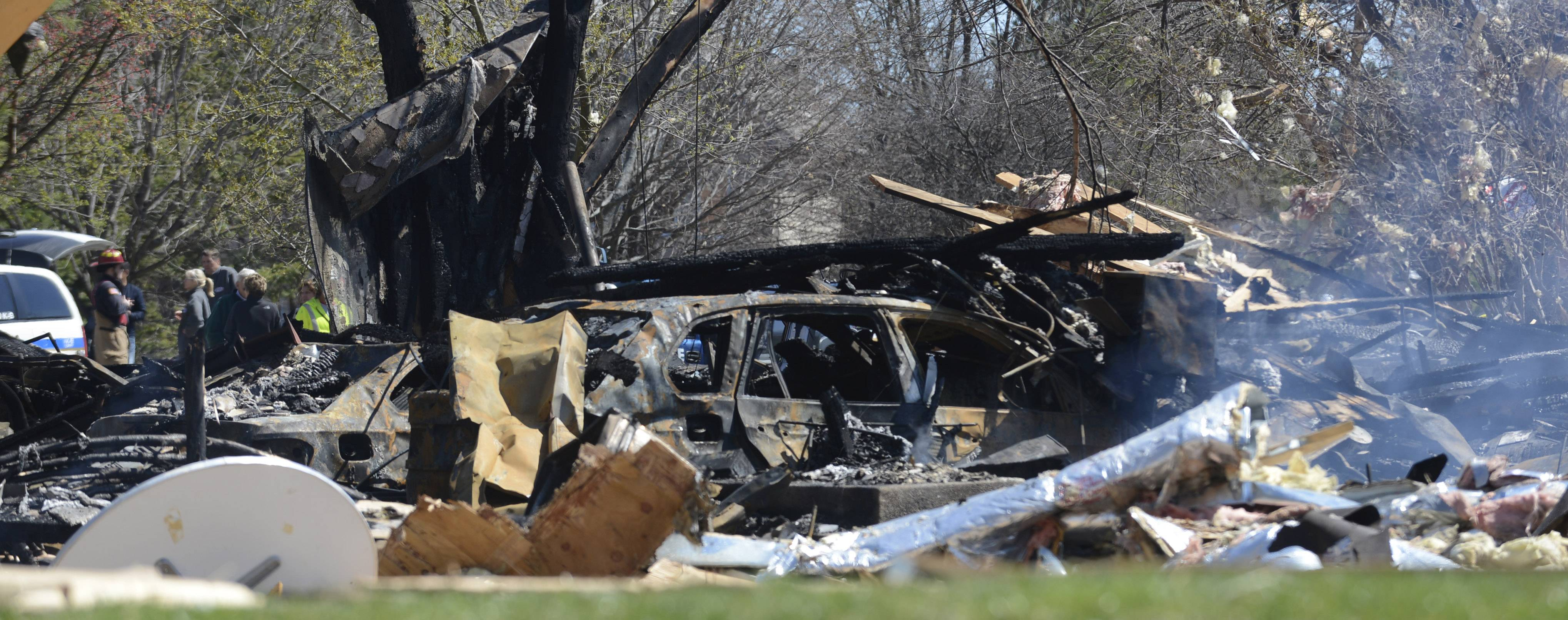 No less than two burned cars rest in the aftermath of Friday's night's explosion of a home in Long Grove.