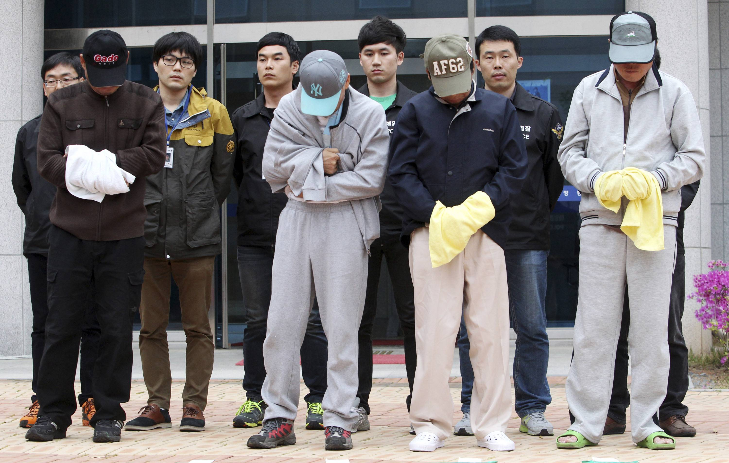 Crew members of sunken ferry Sewol prepare to leave a court which issued their arrest warrant, in Mokpo, South Korea, Saturday, April 26, 2014. All 15 people involved in navigating the South Korean ferry that sank and left scores of people dead or missing are now in custody after authorities on Saturday detained four more crew members, a prosecutor said.
