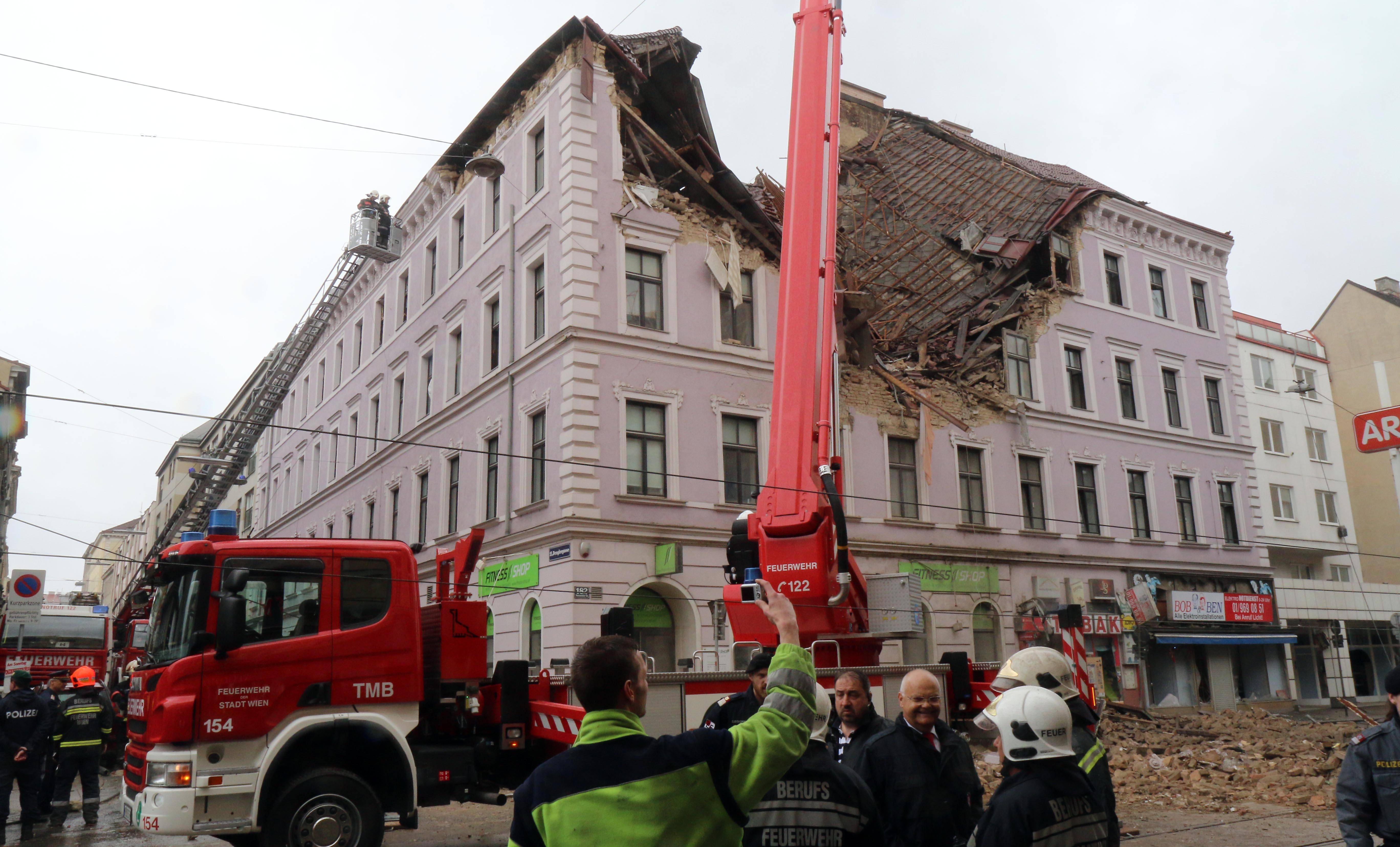 Firefighters and police are busy at a building damaged by an explosion in Vienna, Austria, Saturday, April 26, 2014. Austrian police say at least six people have been injured after the building collapsed following the reported explosion.