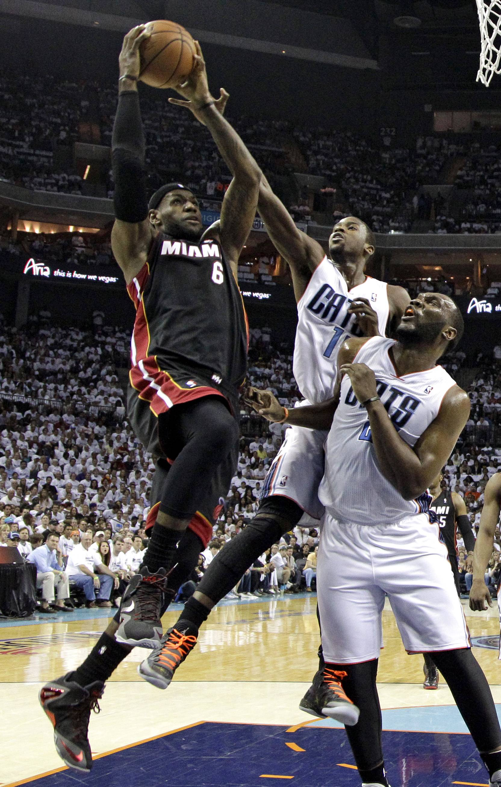 Miami Heat's LeBron James, left, shoots over Charlotte Bobcats' Michael Kidd-Gilchrist, center, and Al Jefferson, right, during Game 3 of an opening-round NBA basketball playoff series Saturday in Charlotte, N.C.