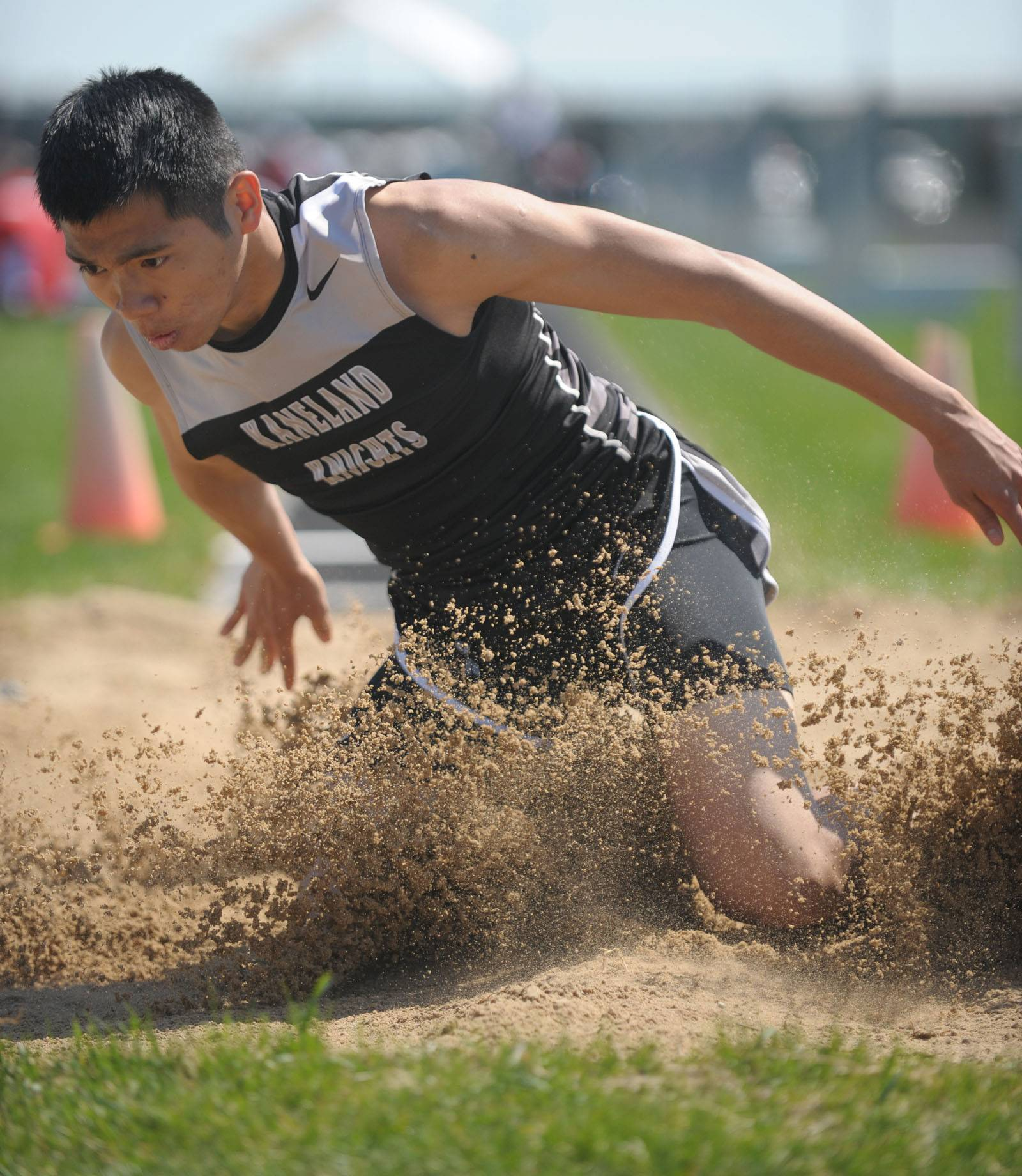 Kaneland's Ben Barnes springs up in the sand after landing in the long jump finals at Kaneland's Peterson Prep Invitational on Saturday, April 26.