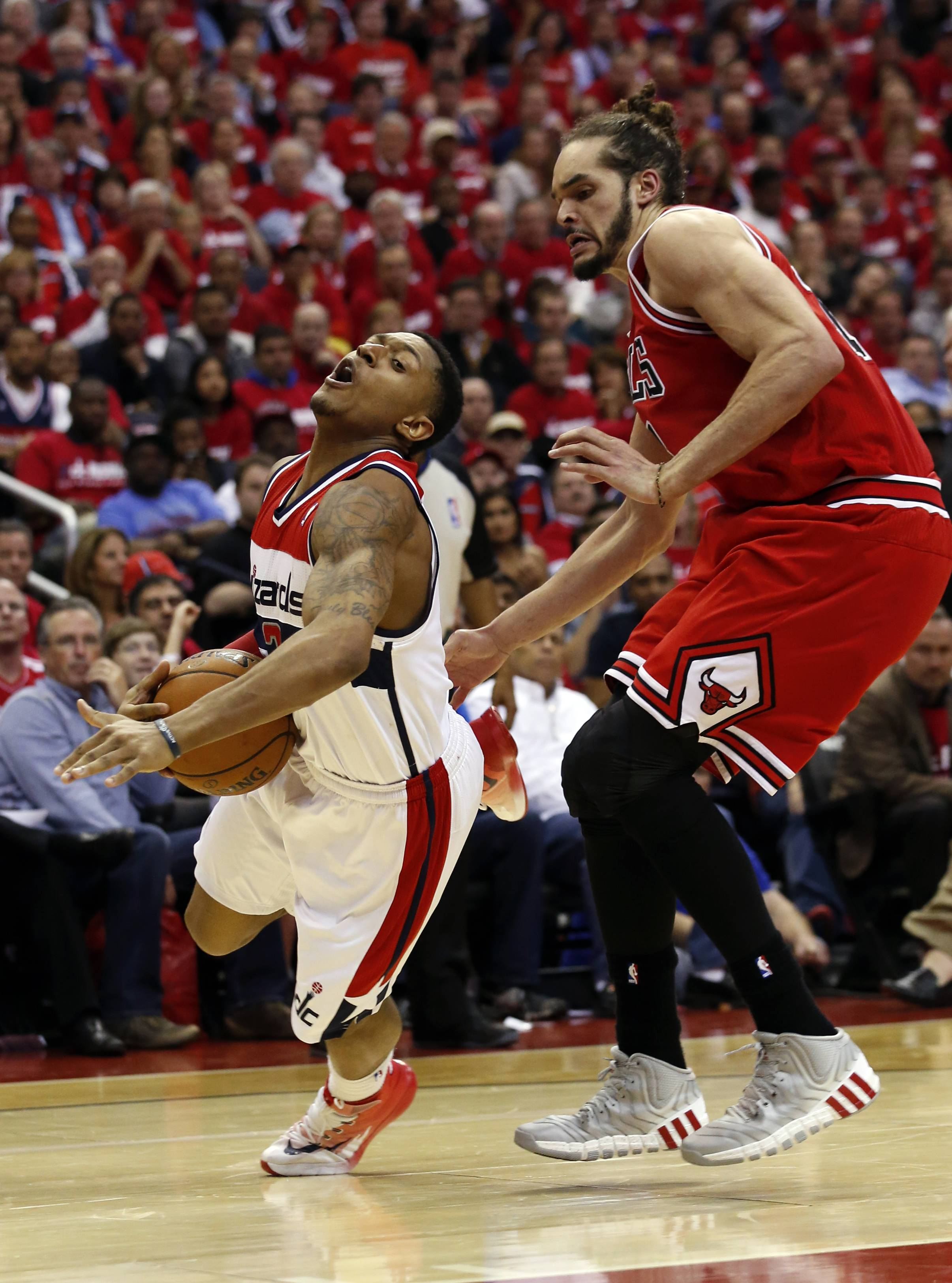 Washington Wizards guard John Wall (2) falls with Chicago Bulls center Joakim Noah (13) defending in the second half of Game 3 of an opening-round NBA basketball playoff series on Friday, April 25, 2014, in Washington. The Bulls won 100-97.