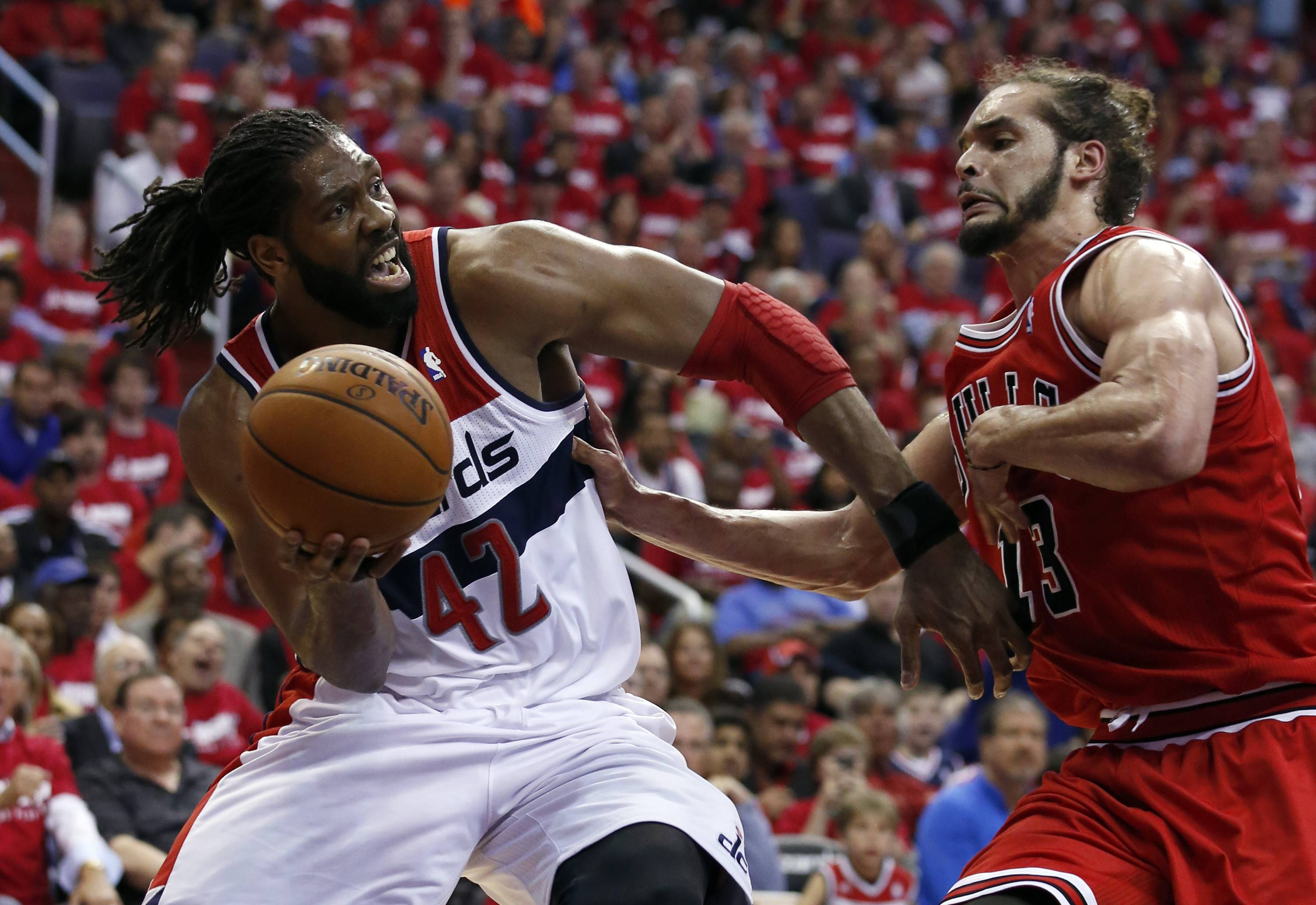 Washington Wizards forward Nene (42), from Brazil, looks to pass as Chicago Bulls center Joakim Noah (13) defends in the second half of Game 3 of an opening-round NBA basketball playoff series, Friday, April 25, 2014, in Washington. The Bulls won 100-97.