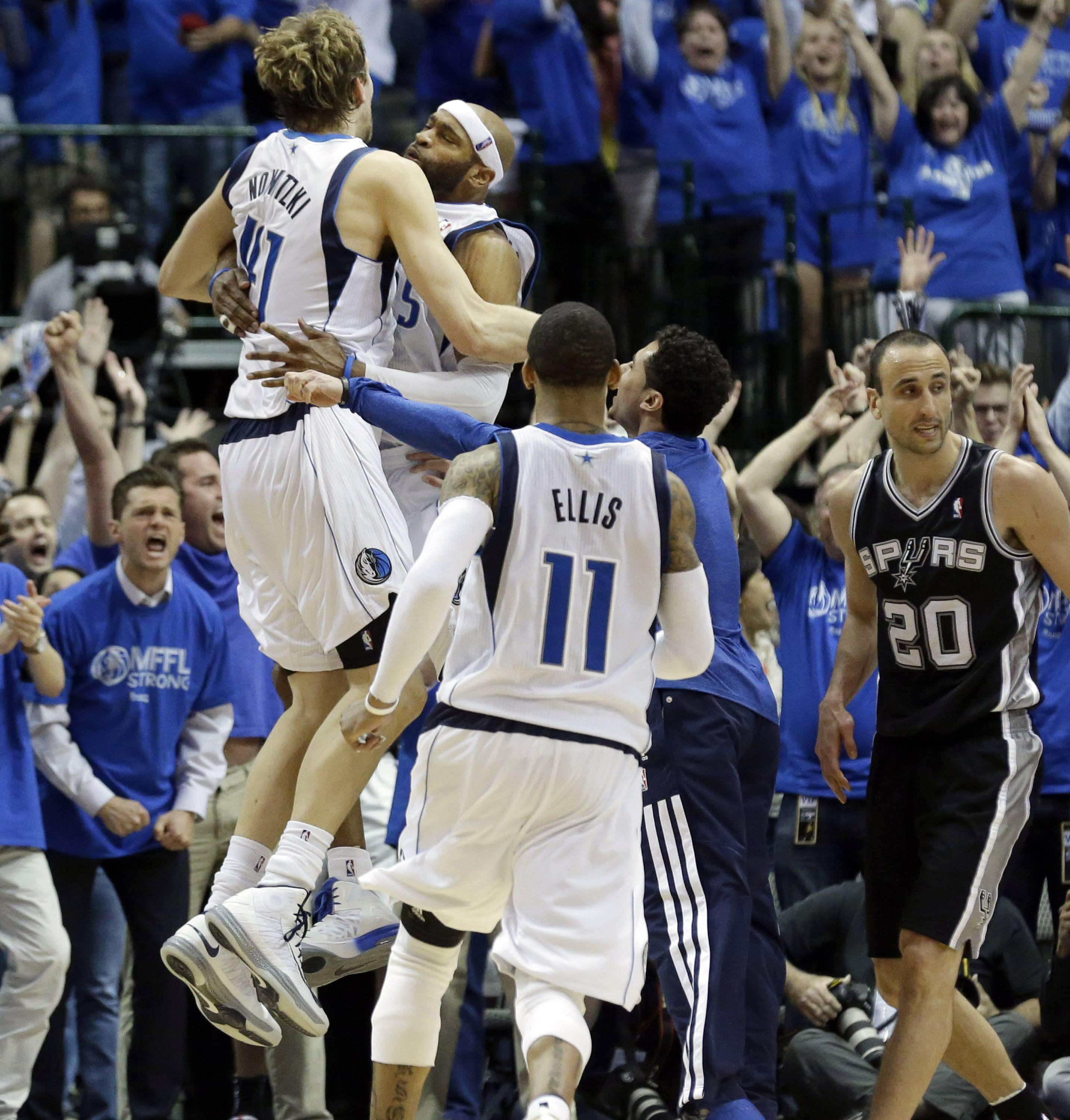 Dallas Mavericks guard Vince Carter, second from left, celebrates with Dirk Nowitzki (41), as teammate Monta Ellis (11) and San Antonio Spurs' Manu Ginobili (20) look on, after Carter made the game-winning 3-point basket at the buzzer of the fourth quarter in Game 3 in the first-round of the NBA basketball playoffs Saturday in Dallas. The Mavericks won 109-108.