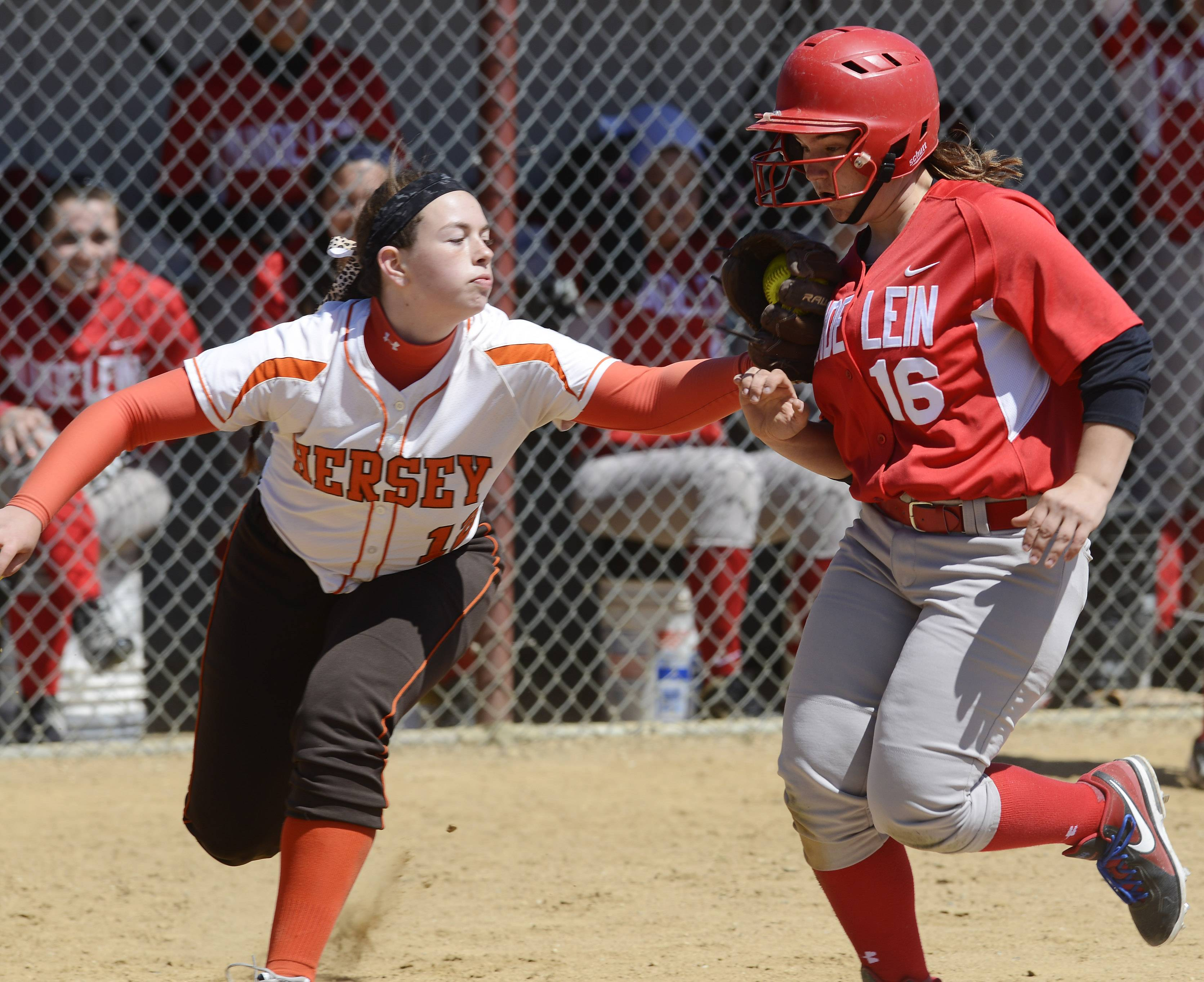 Hersey's Angela Schmiederer, left, tags out Mundelein's Hannah Bulgart in a fifth-inning rundown between third and home during Saturday's game at Mundelein.