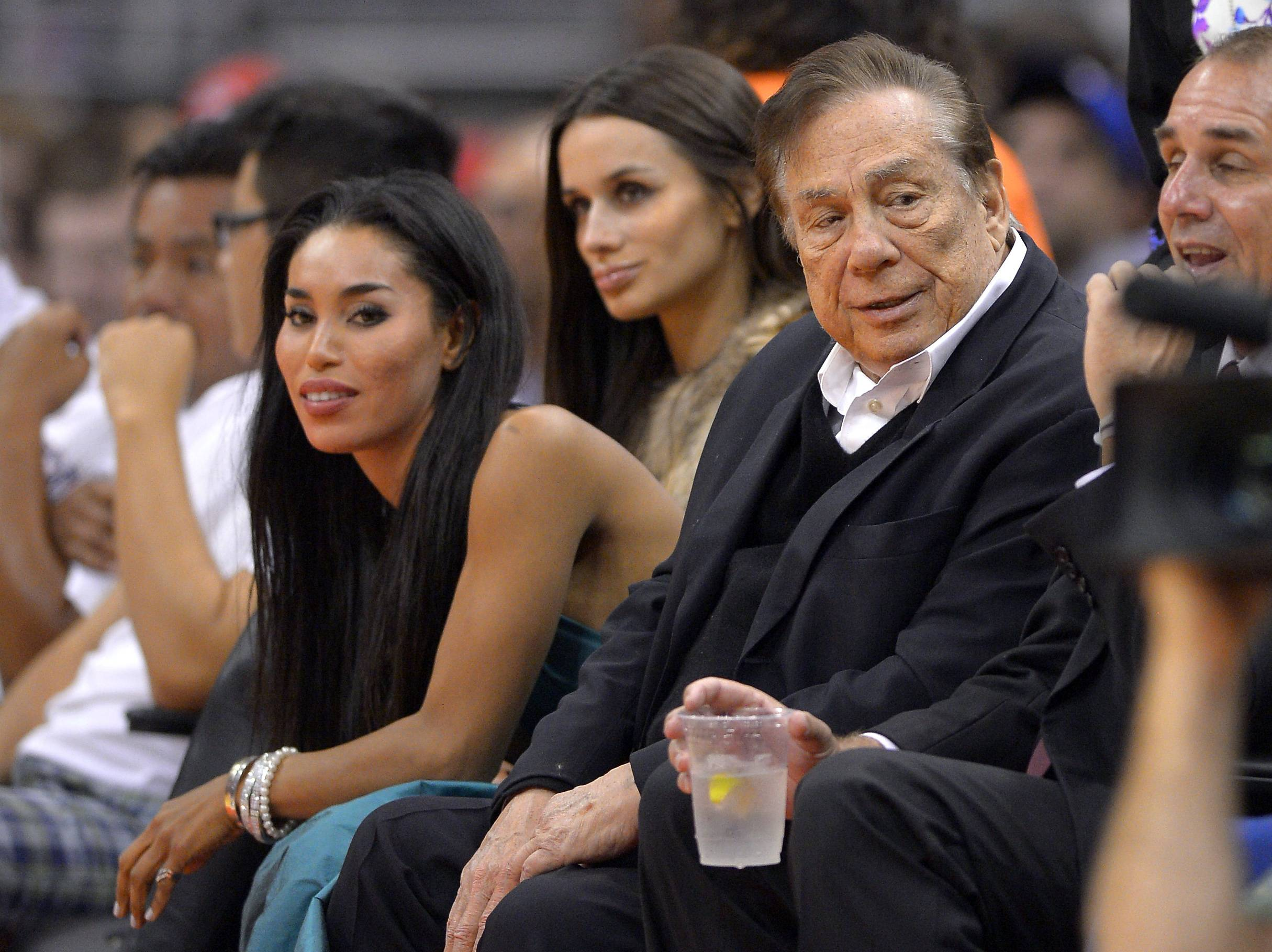 "In this photo taken on Friday, Oct. 25, 2013, Los Angeles Clippers owner Donald Sterling, right, and V. Stiviano, left, watch the Clippers play the Sacramento Kings during the first half of an NBA basketball game in Los Angeles. The NBA is investigating a report of an audio recording in which a man purported to be Sterling makes racist remarks while speaking to Stiviano.  NBA spokesman Mike Bass said in a statement Saturday, April 26, 2014, that the league is in the process of authenticating the validity of the recording posted on TMZ's website. Bass called the comments ""disturbing and offensive."""