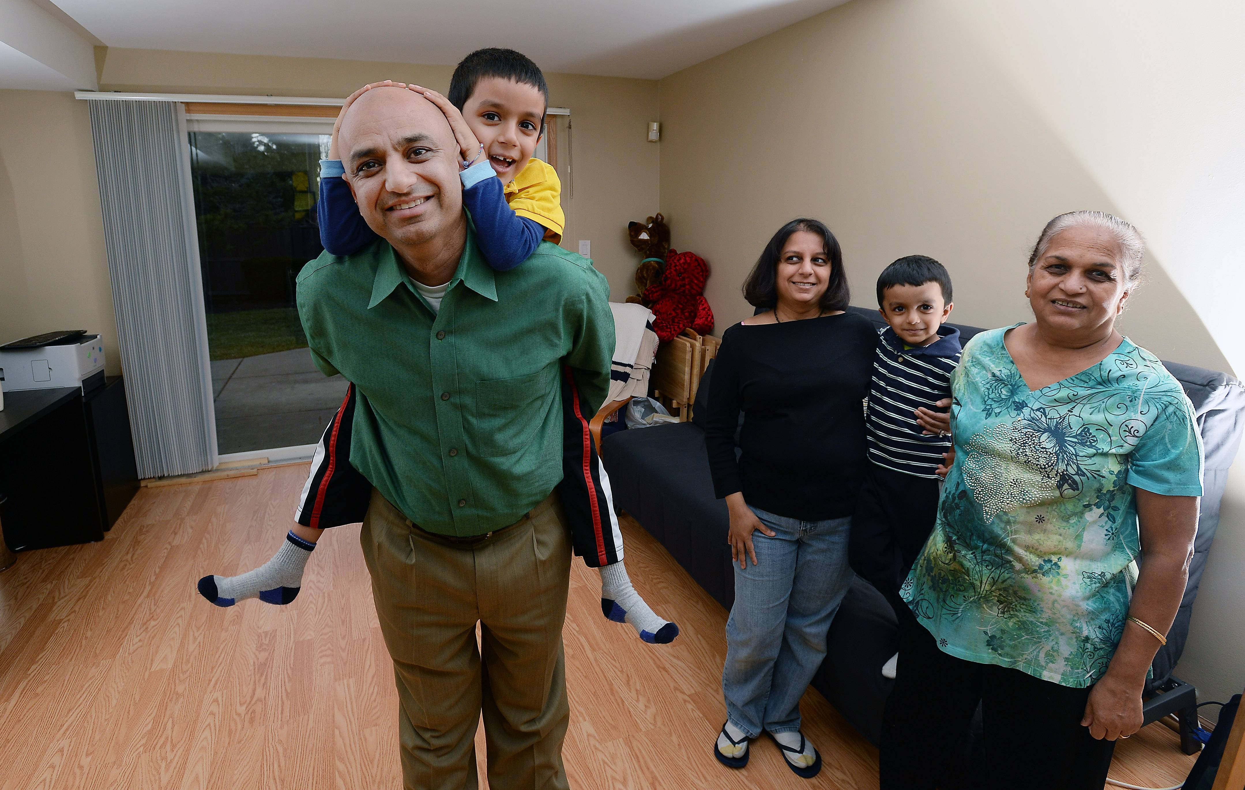 The Bhatt family of Mount Prospect love their new multigenerational home. Jaydip and his wife Devyani, center, live with Devyani's mother, Lili Patel, right, as well as their two kids, Raveen, 6, (on his dad's back) and Jushnn, 4.