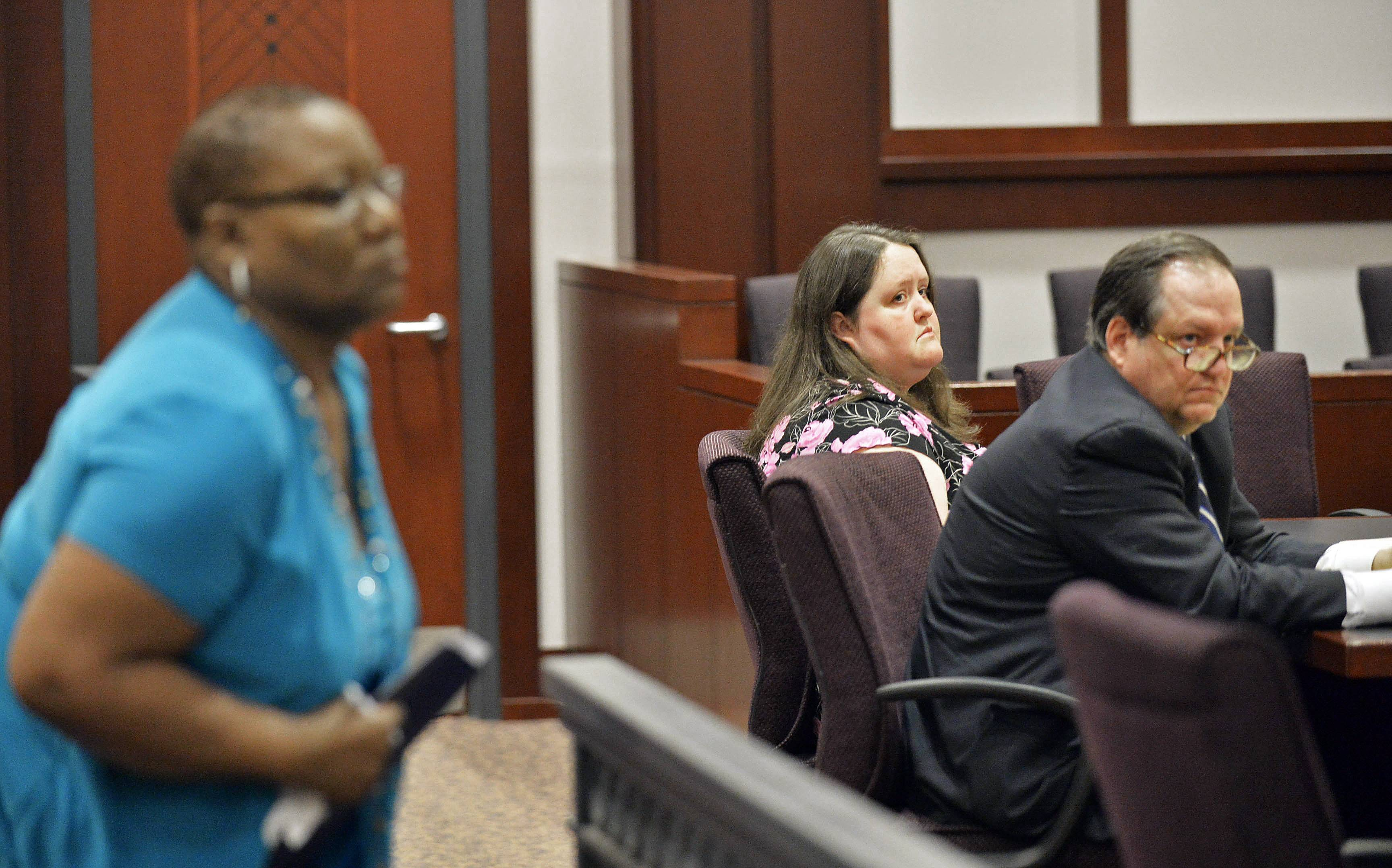Rachael Michelle Rapraeger, center, sits with her attorney, Floyd Buford, after Sharon Holmes, left, read her statement to a Houston County Superior Court, in Perry, Ga., during a sentencing hearing. Rapraeger pleaded guilty this month to 10 misdemeanor charges of reckless conduct and one felony charge of computer forgery after she admitted falsifying hundreds of mammogram reports, one of whom's was Sharon Holmes'.