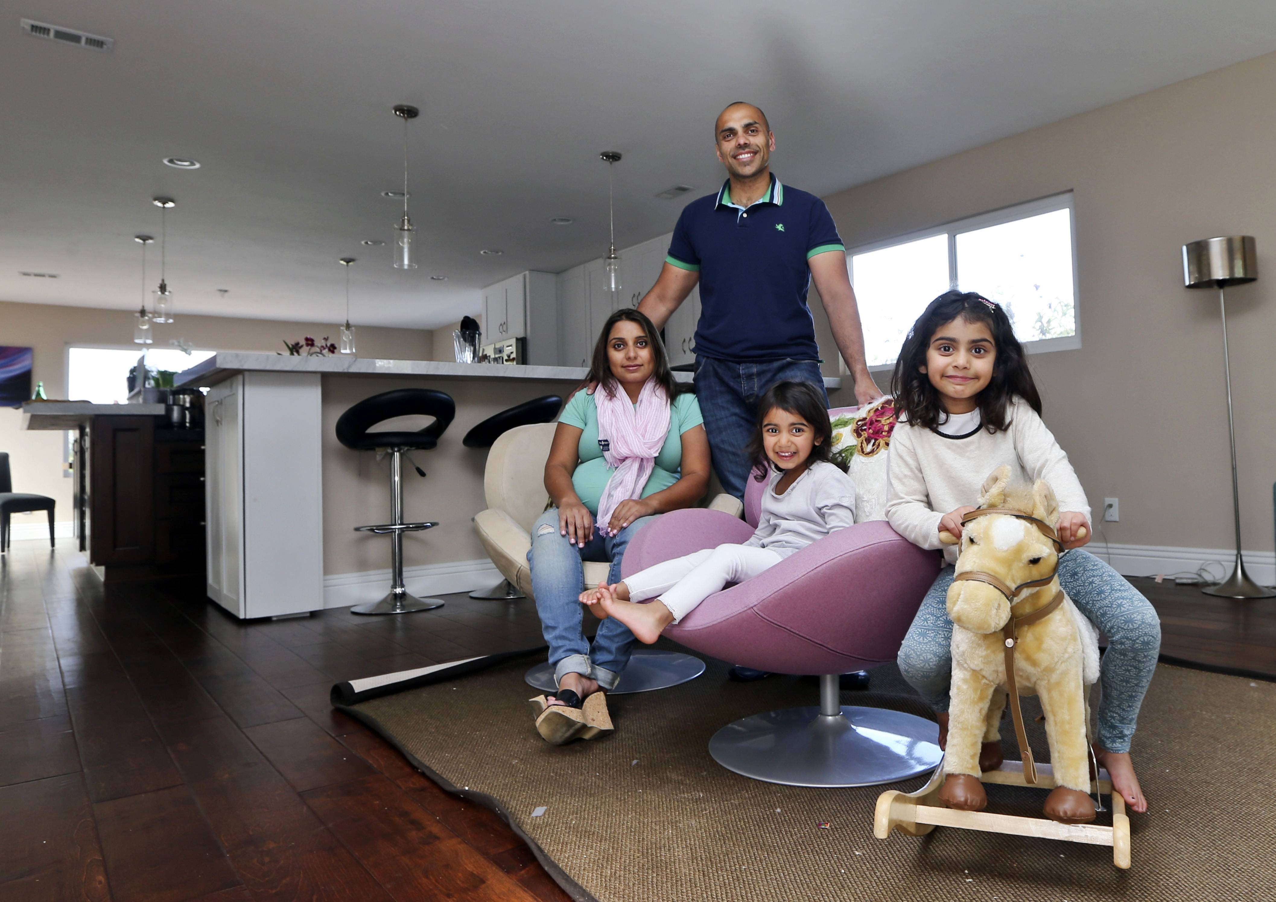 The Jaswal family, Imran, standing, wife Aniqa, left, and daughters, Arissa, right, and Jayda, pose for photos in the family room at their home in La Jolla, Calif. The couple bought the four-bedroom house about 10 minutes from the beach in February. Once Imran's management consulting business began flourishing, the couple felt comfortable enough after years of renting to buy their first home.
