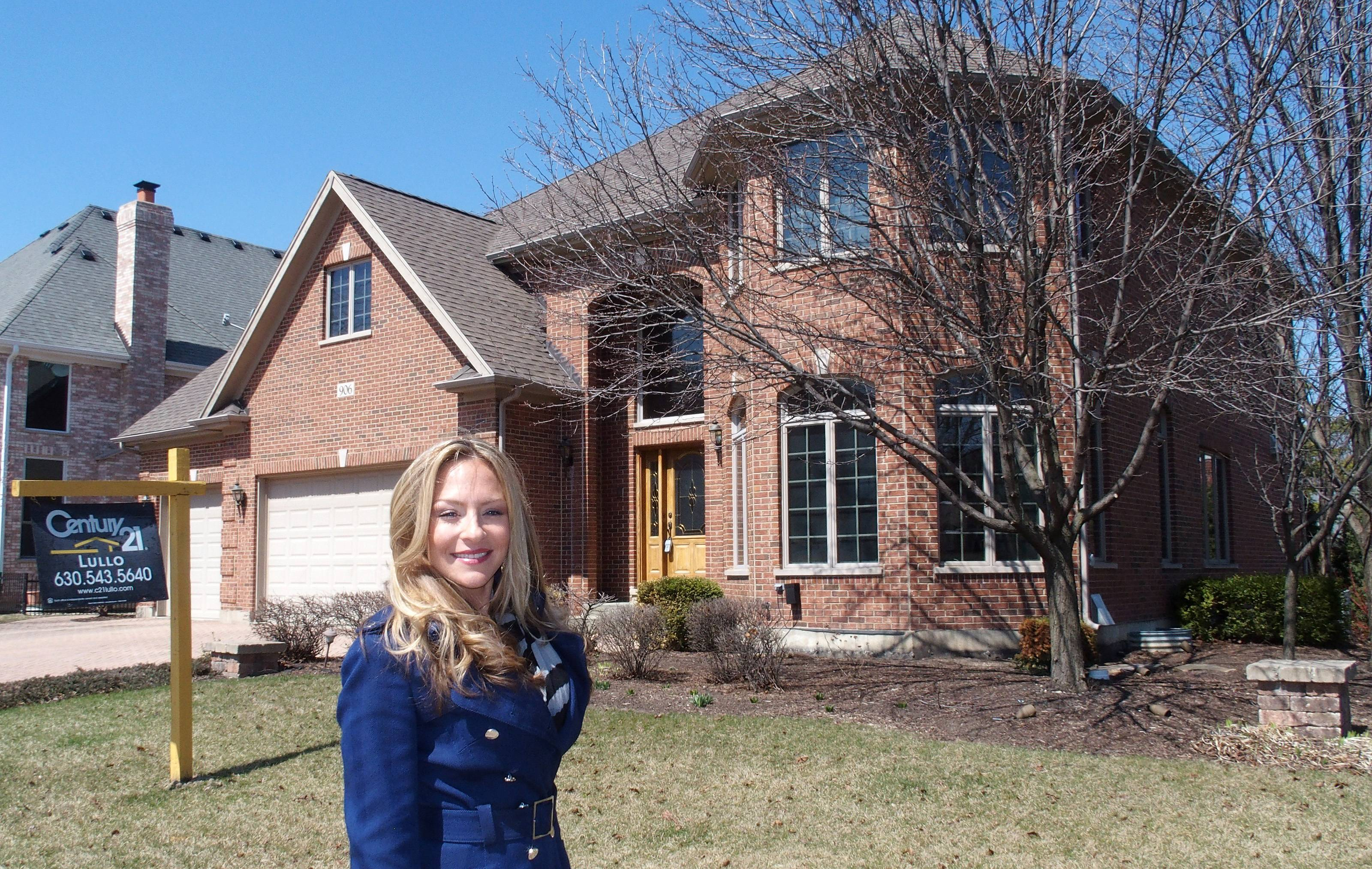 Realtor Deanna Lullo in front of a home she has listed. Lullo says more families are opting to buy homes to accommodate three generations.