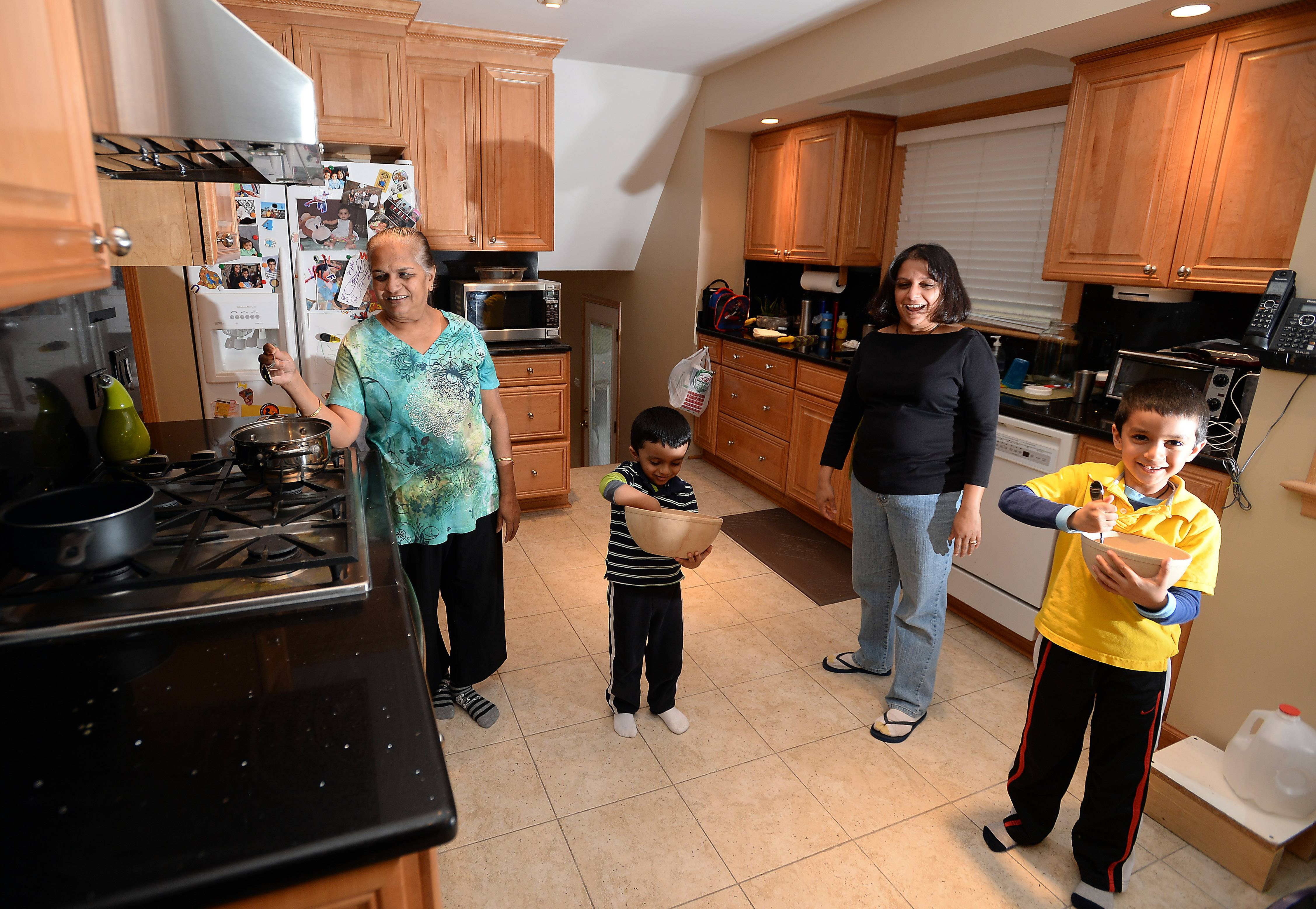 The Bhatt family of Mount Prospect make dinner in the  family's kitchen.