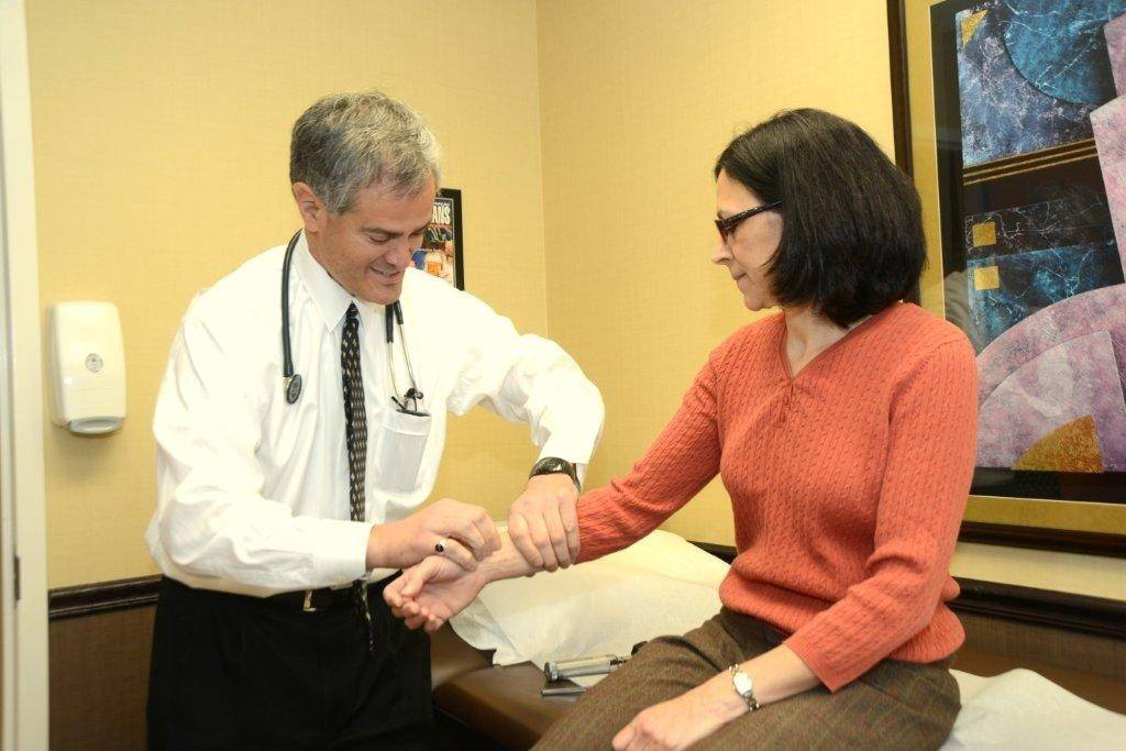 Dr. Evan Lipkis, a physician based in Glenview, checks the pulse of a patient.