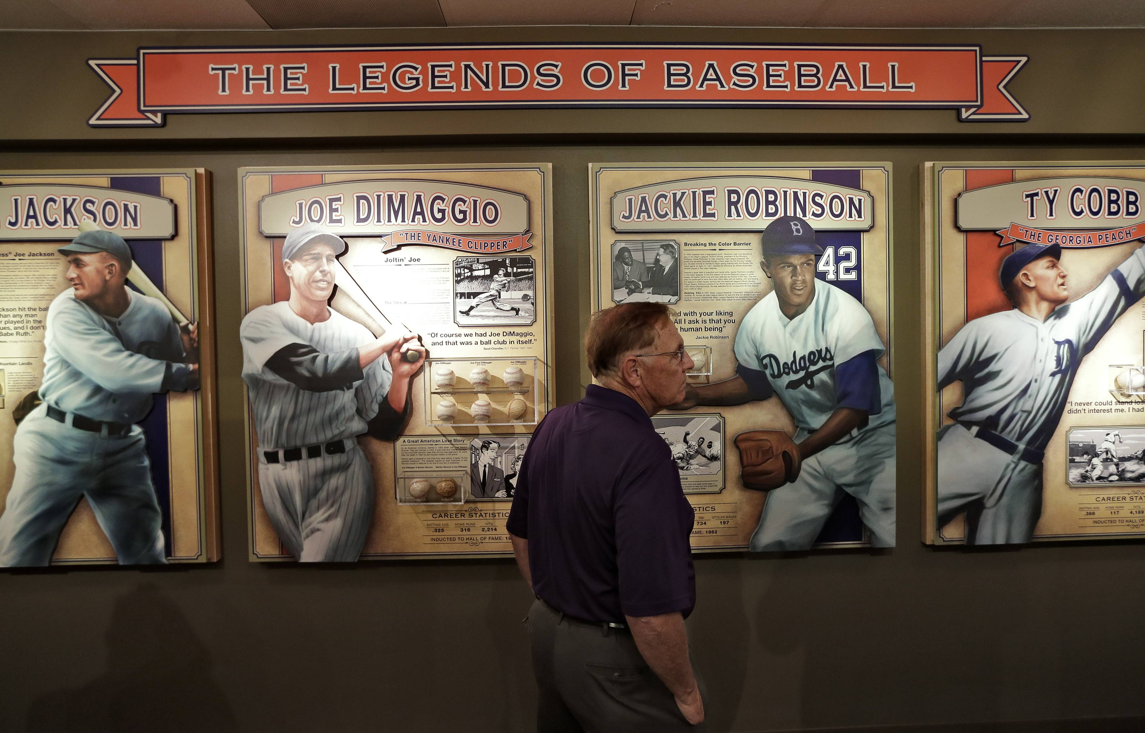 Visitors to the St. Petersburg History Museum view some of Dennis Schrader's autographed baseballs in St. Petersburg, Fla.