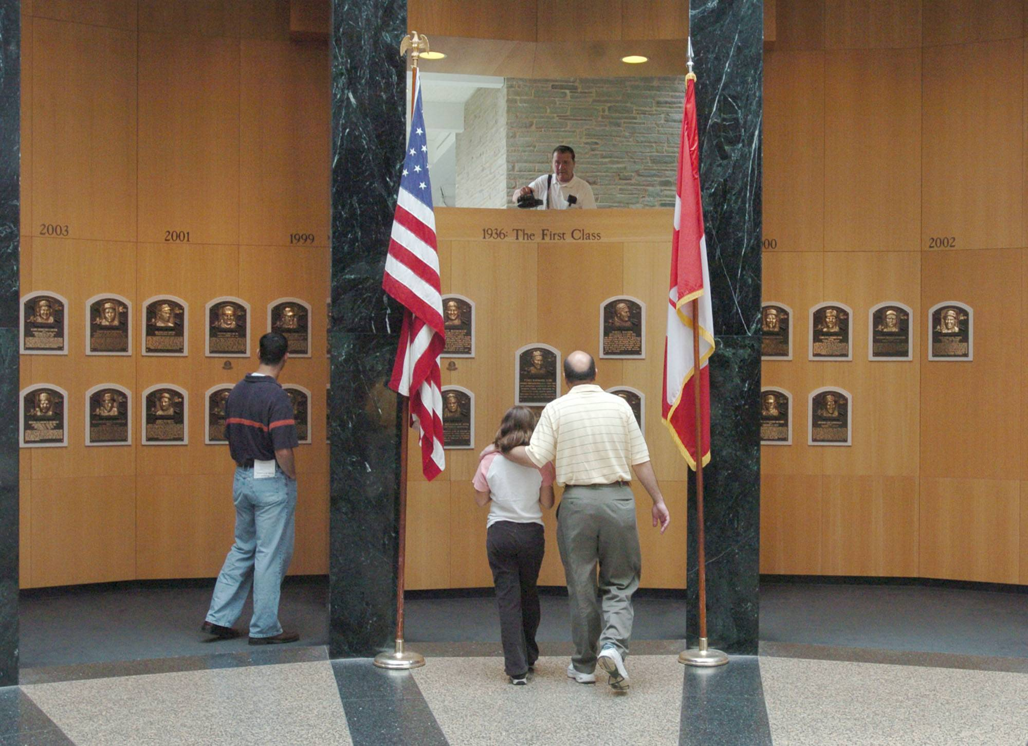 Museum patrons view plaques of recent inductees into the National Baseball Hall of Fame and Museum in Cooperstown, N.Y.