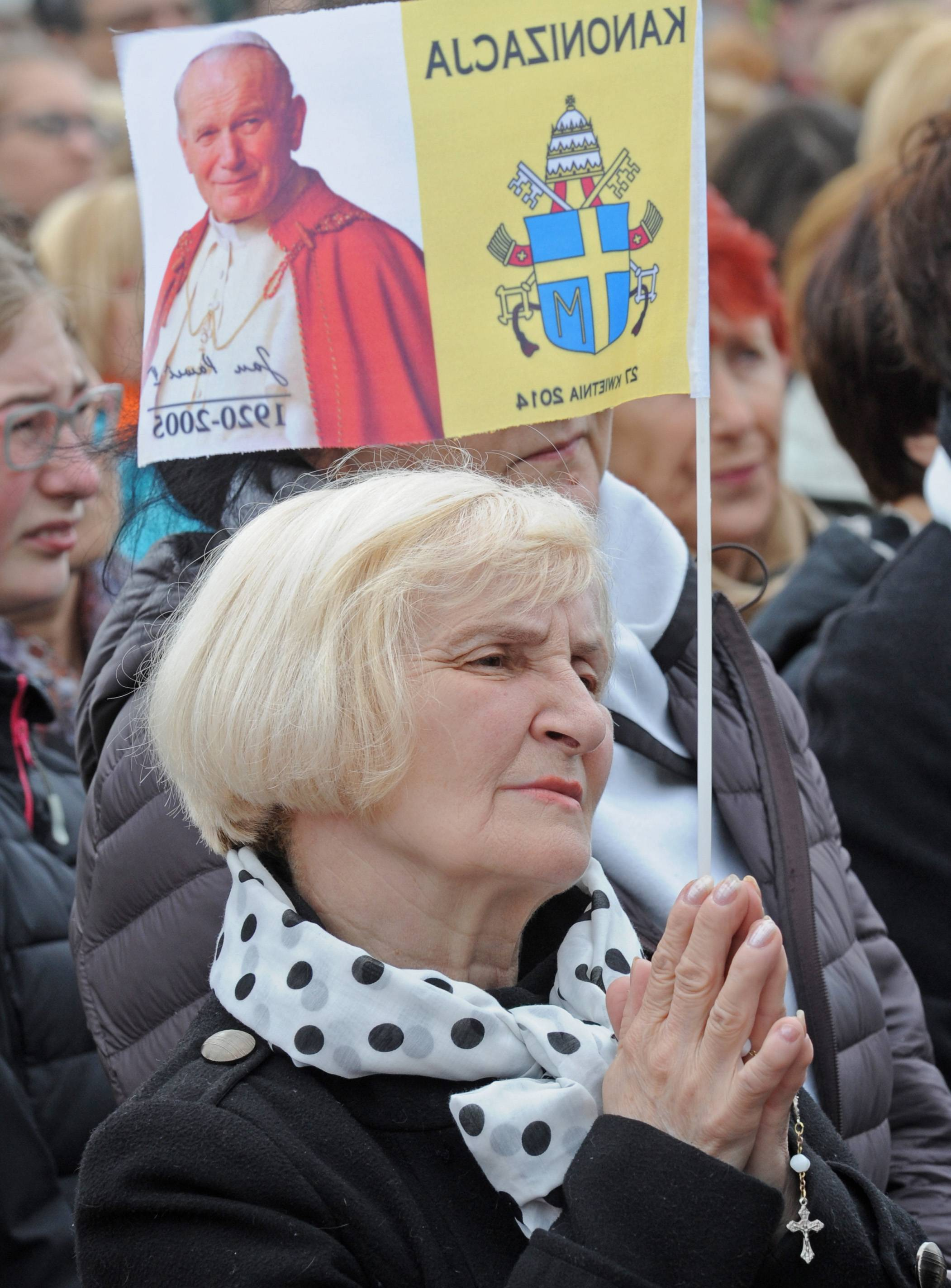 A woman prays during a public live viewing of the canonization mass from the Vatican in Warsaw, Poland, Sunday. Several thousands of faithful watched the live transmission as Pope Francis, aided by emeritus Pope Benedict XVI declared John Paul II and John XXIII saints, in an unprecedented ceremony involving four popes.