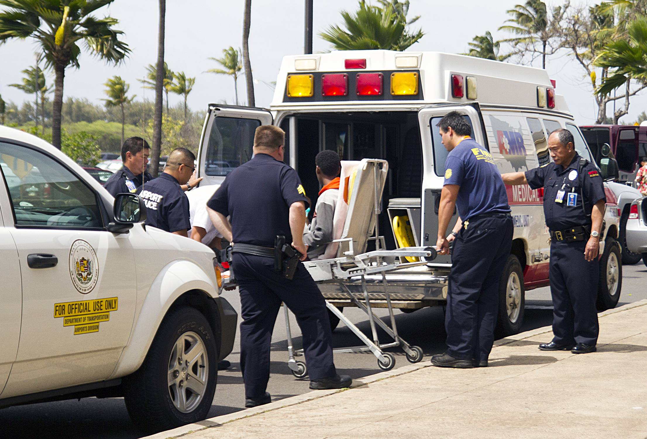 A 15-year-old boy, seen sitting on a stretcher center, who stowed away in the wheel well of a flight from San Jose, Calif., to Hawaii is loaded into an ambulance at Kahului Airport in Kahului, Maui, April 20.