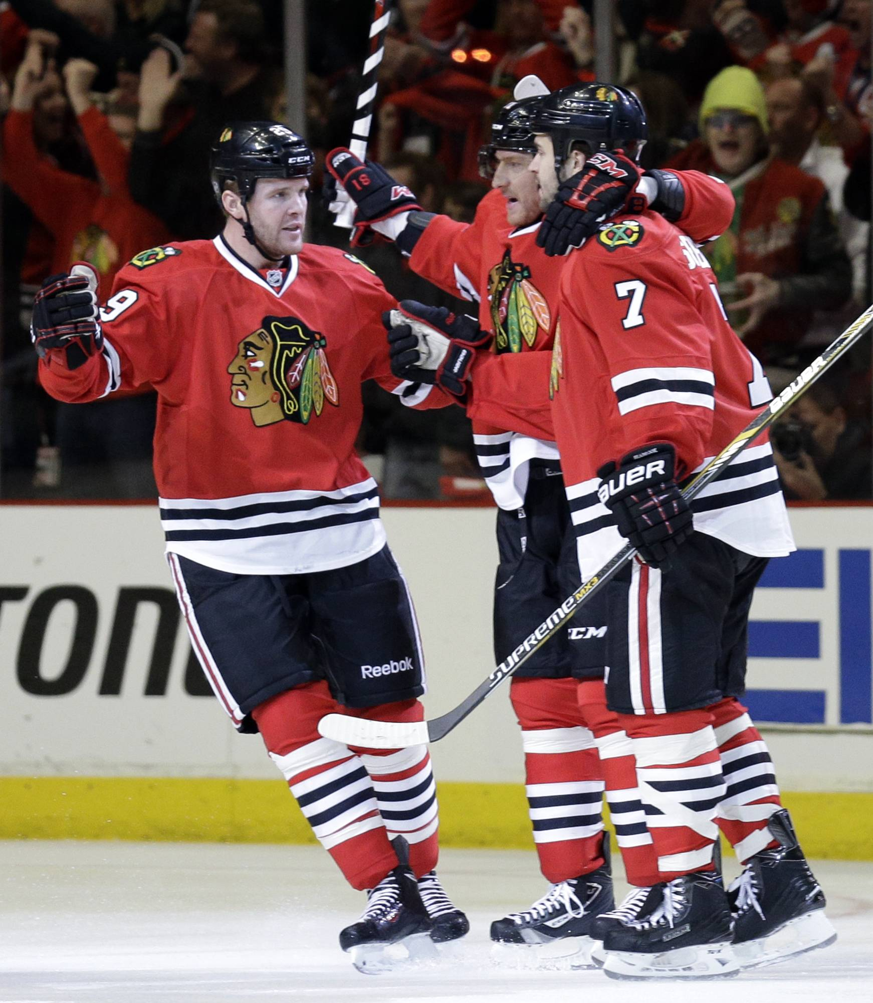Chicago Blackhawks' Bryan Bickell, left, celebrates with teammate Marian Hossa, center, and Brent Seabrook (7) after scoring a goal against the St. Louis Blues during the first period.
