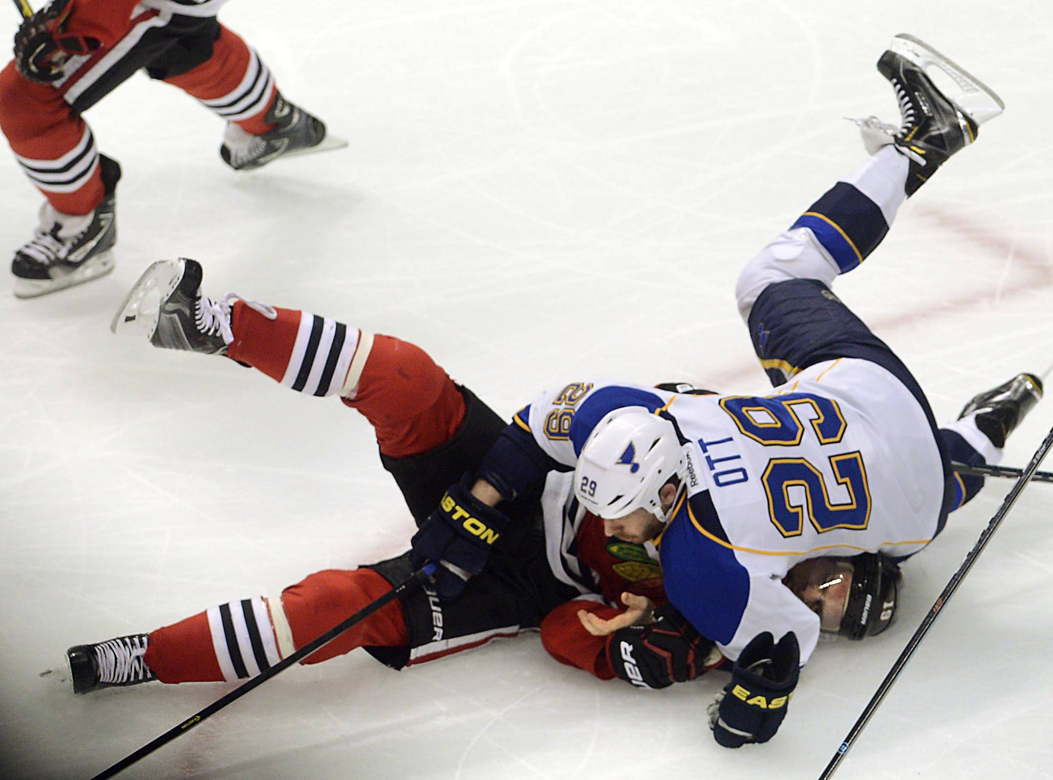 Chicago Blackhawks center Jonathan Toews is held down by St. Louis Blues center Steve Ott.