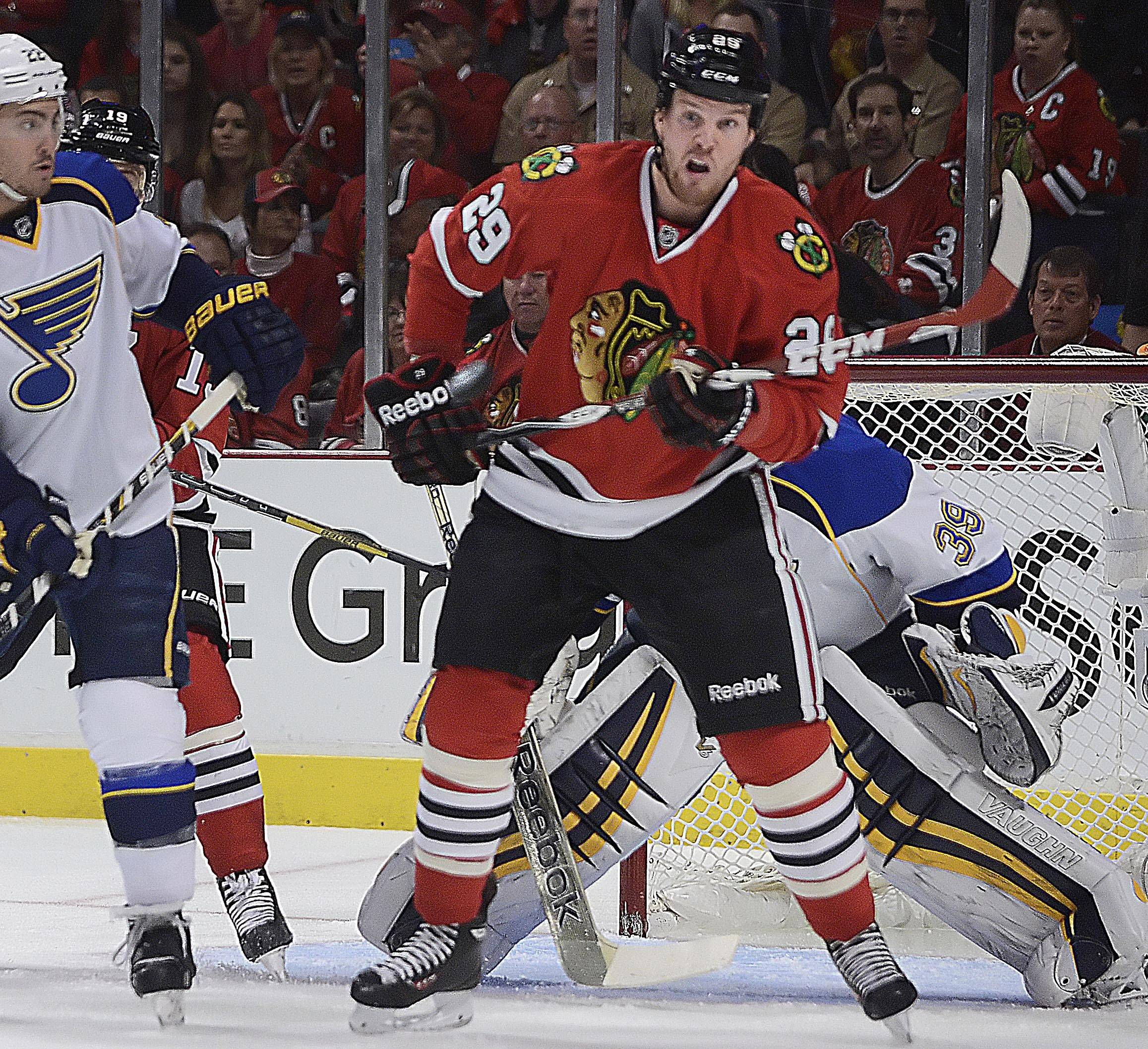 Chicago Blackhawks left wing Bryan Bickell lifts his stick to deflect the puck (near his right glove) into the net against the St. Louis Blues in the first period Sunday in Game 6 of the NHL first round playoffs at the United Center in Chicago.