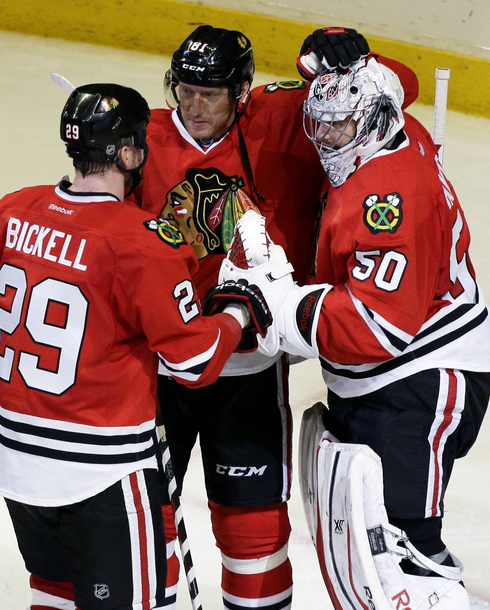 Chicago Blackhawks goalie Corey Crawford (50) celebrates with teammates Marian Hossa (81) and Bryan Bickell (29) after they defeated the St. Louis Blues 5-1 in Game 6.