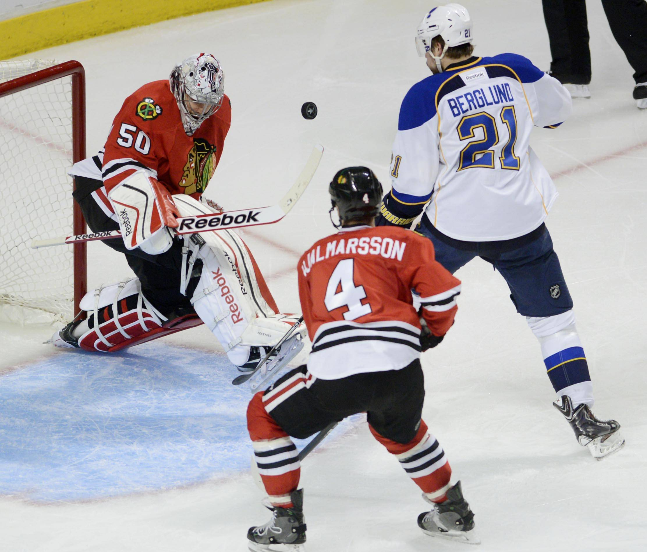 Chicago Blackhawks goalie Corey Crawford deflects a shot as St. Louis Blues center Patrik Berglund and Chicago Blackhawks defenseman Niklas Hjalmarsson close in on the net Sunday in Game 6 of the NHL first round playoffs at the United Center in Chicago.