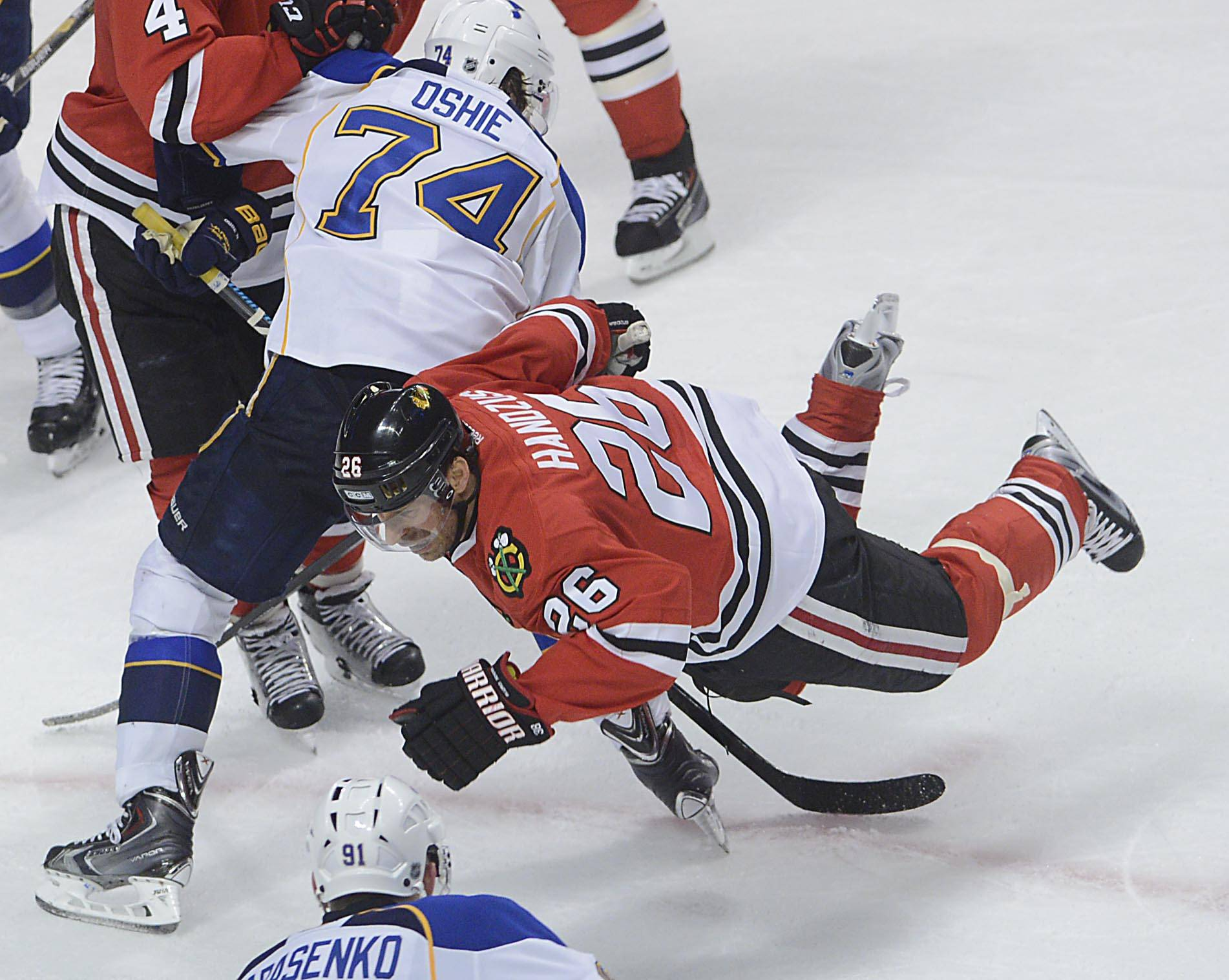 Chicago Blackhawks center Michal Handzus is tripped by St. Louis Blues right wing T.J. Oshie Sunday in Game 6 of the NHL first round playoffs at the United Center in Chicago.