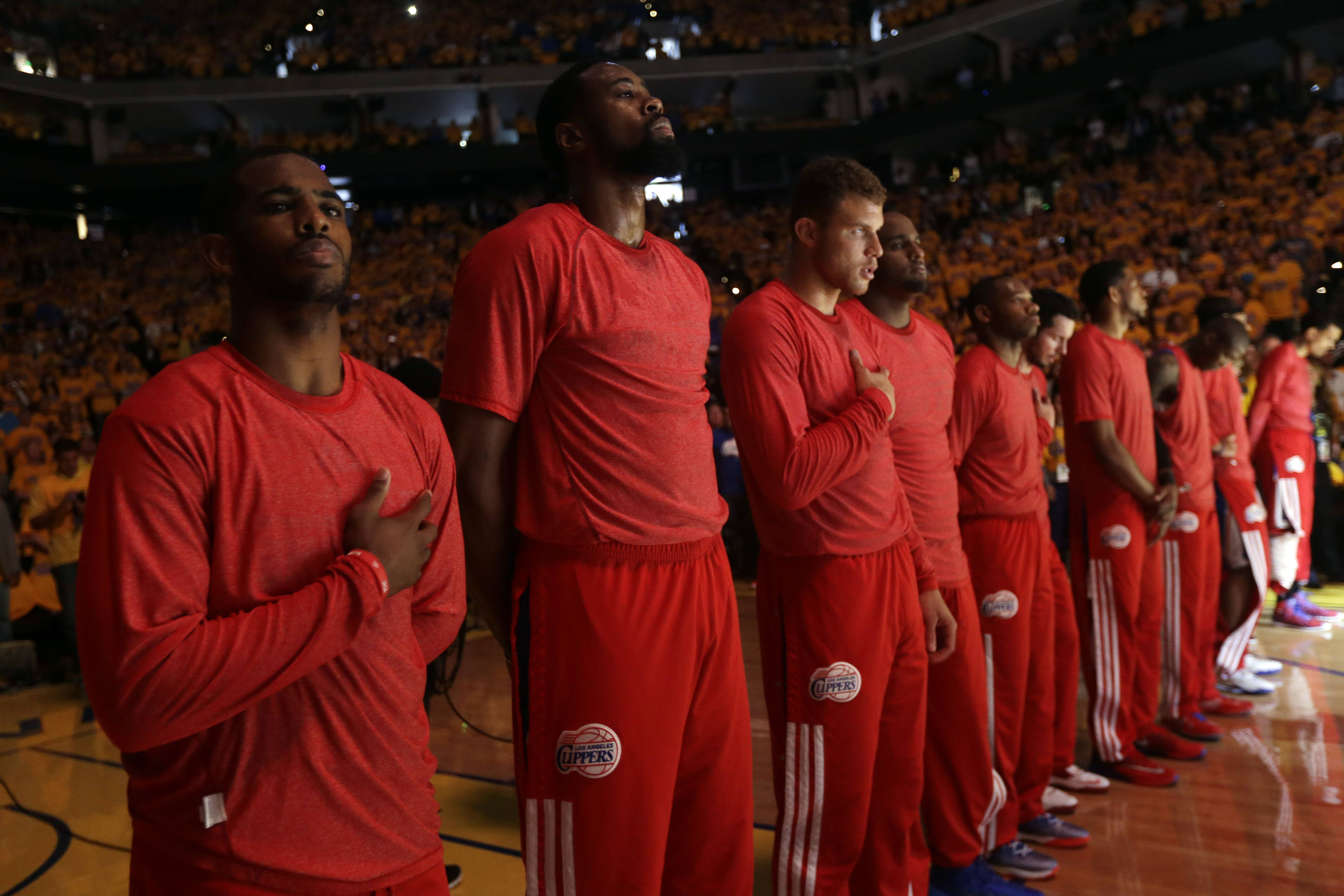 Members of the Los Angeles Clippers listen to the national anthem before Game 4 of an opening-round NBA basketball playoff series against the Golden State Warriors on Sunday, April 27, 2014, in Oakland, Calif. The Clippers chose not to speak publicly about owner Donald Sterling. Instead, they made a silent protest. The players wore their red Clippers' shirts inside out to hide the team's logo.
