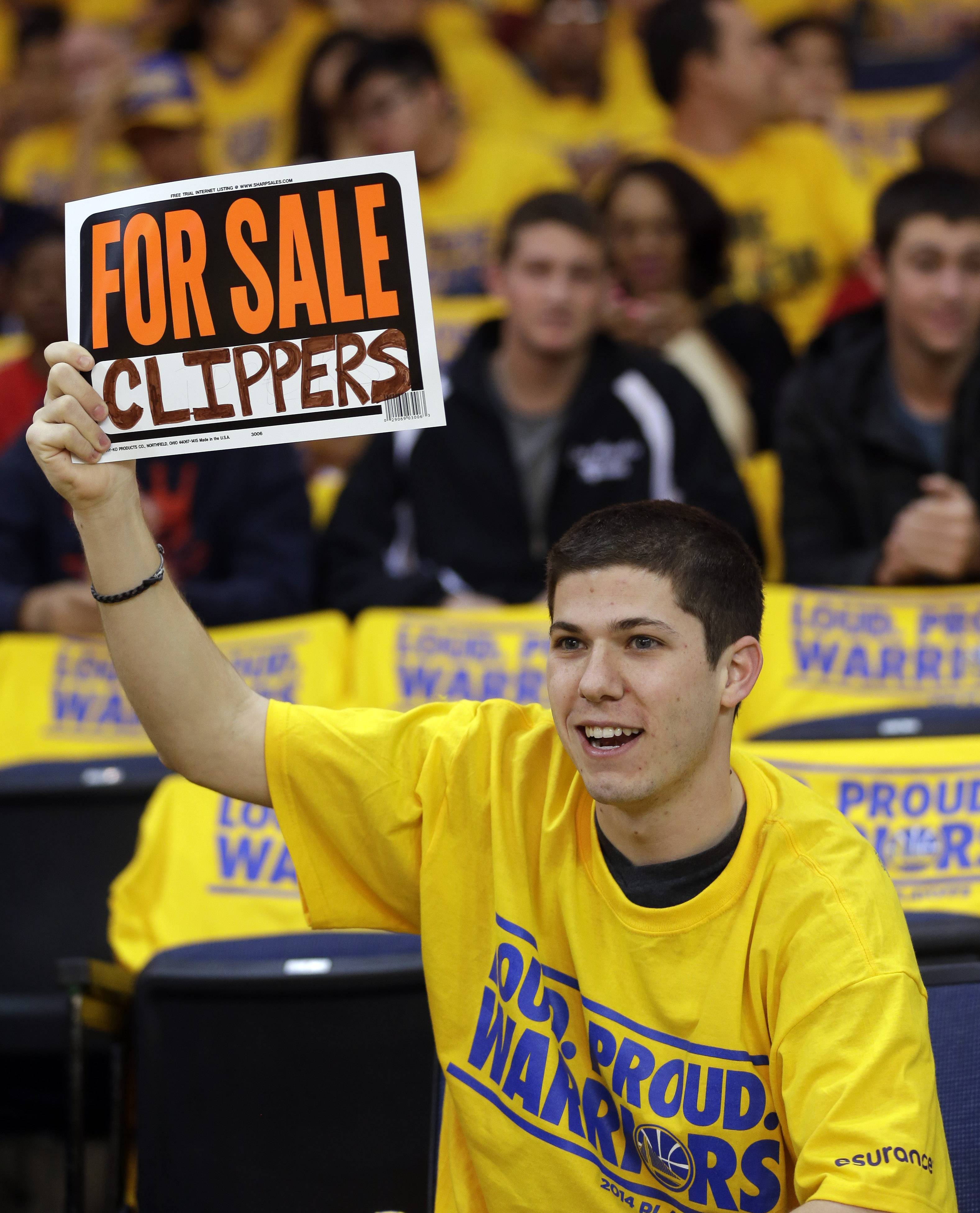 Fan Kevin Phillips holds up a sign making light of controversies surrounding the Los Angeles Clippers before Game 4 of an opening-round NBA basketball playoff series against the Golden State Warriors on Sunday, April 27, 2014, in Oakland, Calif.