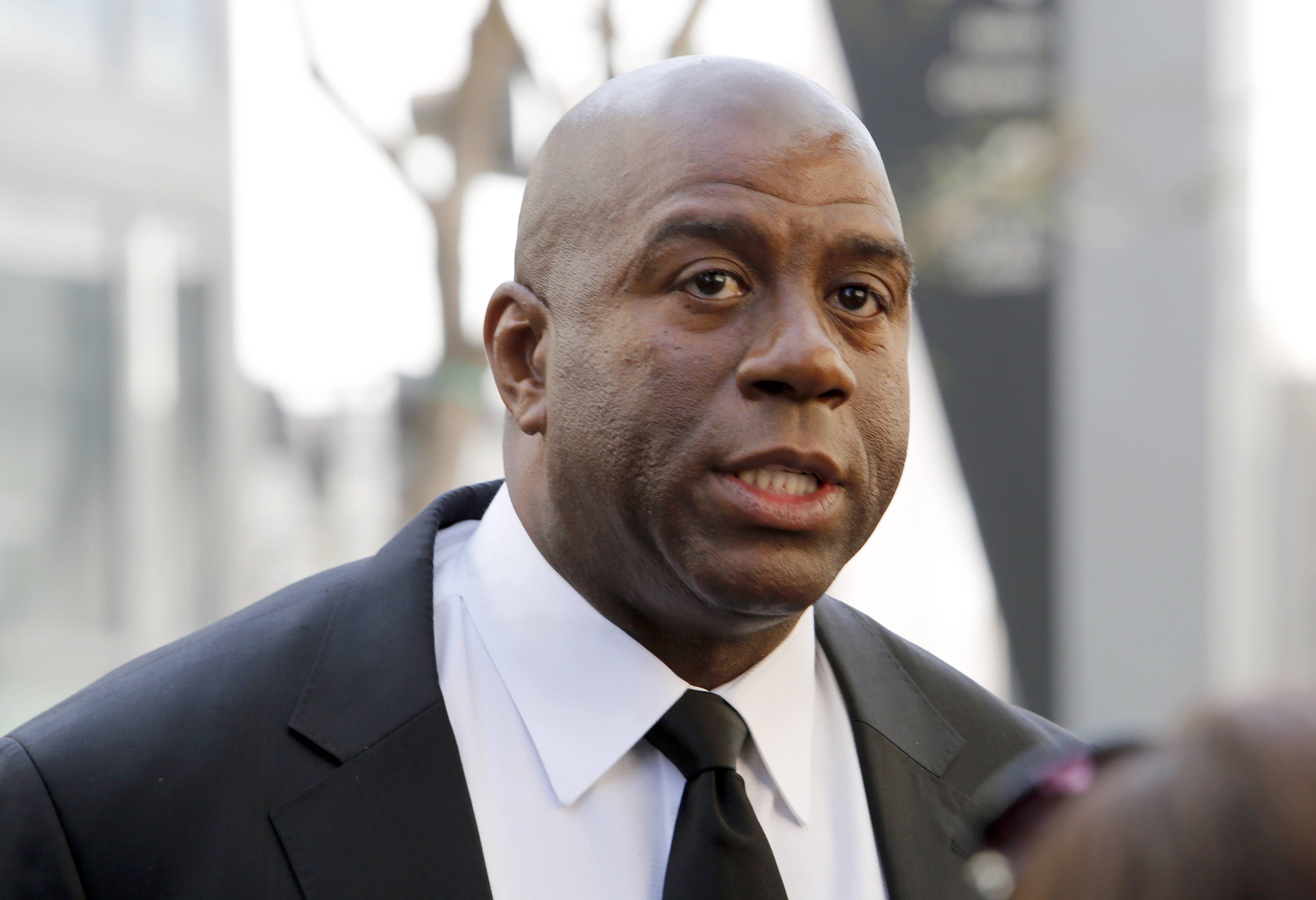 "In this Feb. 21, 2013, file photo, former Los Angeles Lakers player Earvin ""Magic"" Johnson arrives at a memorial service for Jerry Buss in Los Angeles. Johnson is calling upon NBA Commissioner Adam Silver to ""come down hard"" on Los Angeles Clippers owner Donald Sterling, who is alleged to have made racially charged comments. Johnson was a subject of the comments Sterling allegedly made on an audio recording obtained and released by TMZ."