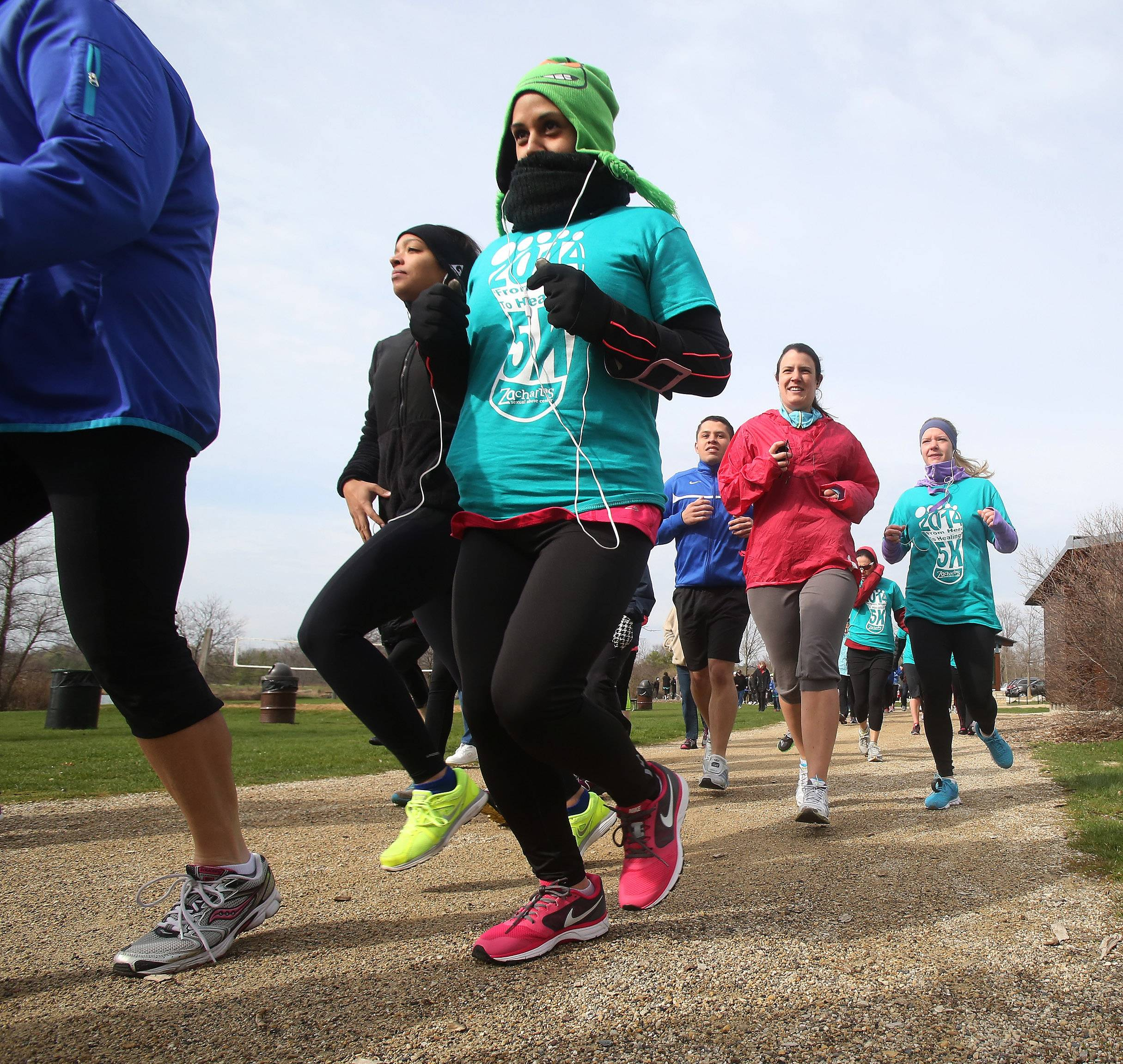 "Priscilla Rios of Carpentersville bundles up as she runs during the second annual Zacharias Sexual Abuse Center 5K Run/Walk Sunday at Independence Grove Forest Preserve near Libertyville. More than 300 people attended the fundraising event called ""From Here To Healing."""