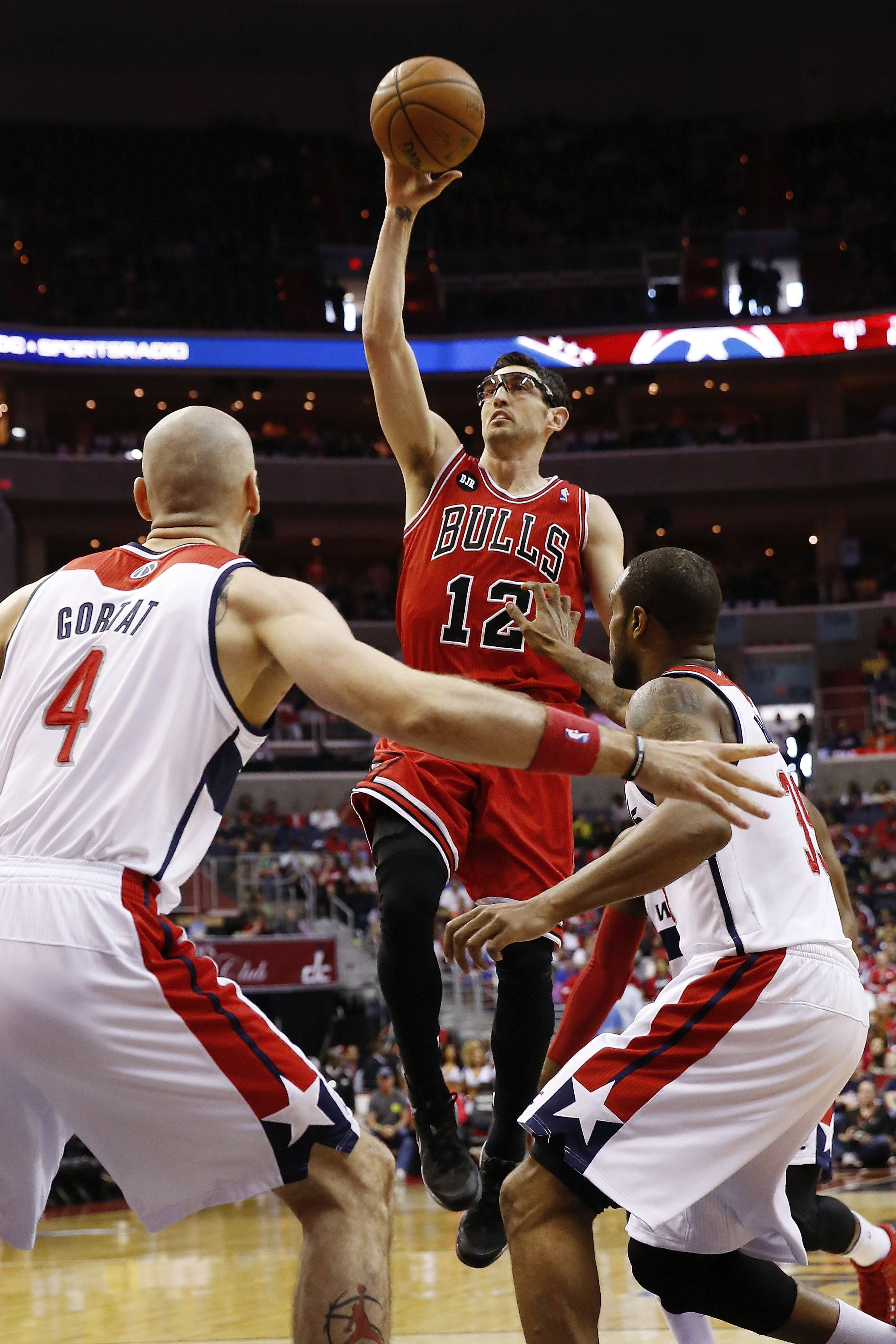 Chicago Bulls guard Kirk Hinrich (12) shoots over Washington Wizards center Marcin Gortat (4), from Poland, and Trevor Booker, right, during the first half.