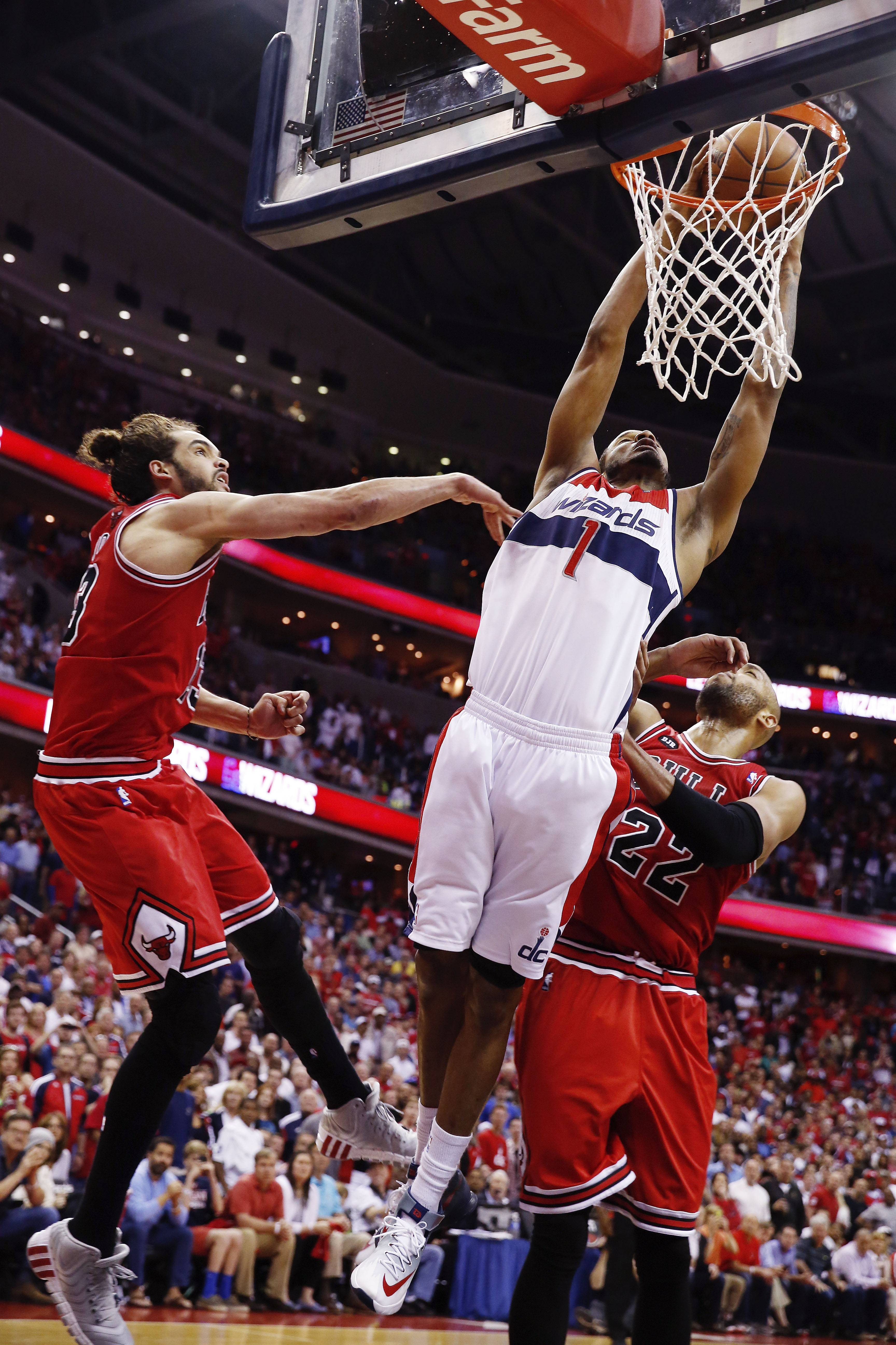 Washington Wizards forward Trevor Ariza (1) dunks the ball between Chicago Bulls center Joakim Noah, left, and forward Taj Gibson (22) during the second half. The Wizards defeated the Bulls 98-89.