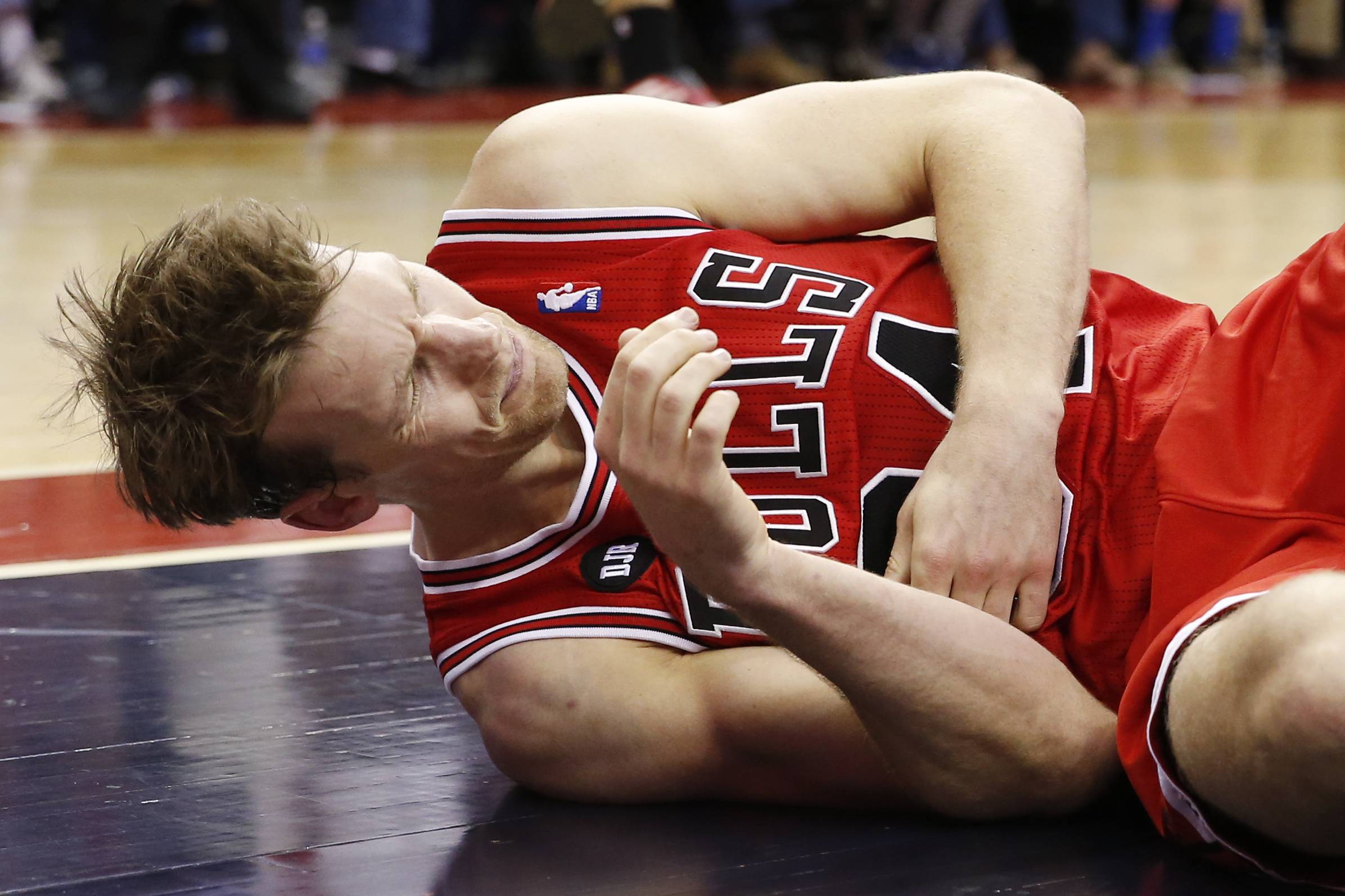 Chicago Bulls forward Mike Dunleavy lies on the court after an injury during the second half.