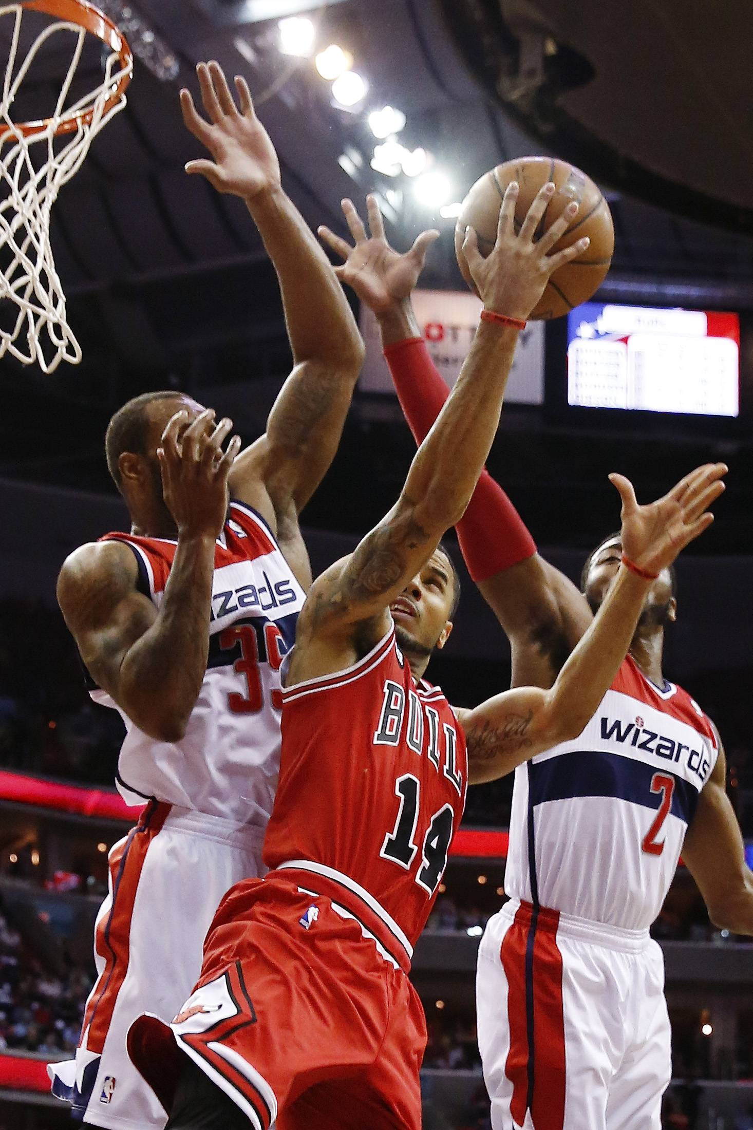 Chicago Bulls guard D.J. Augustin (14) shoots between Washington Wizards forward Trevor Booker (35) and guard John Wall (2) during the first half.