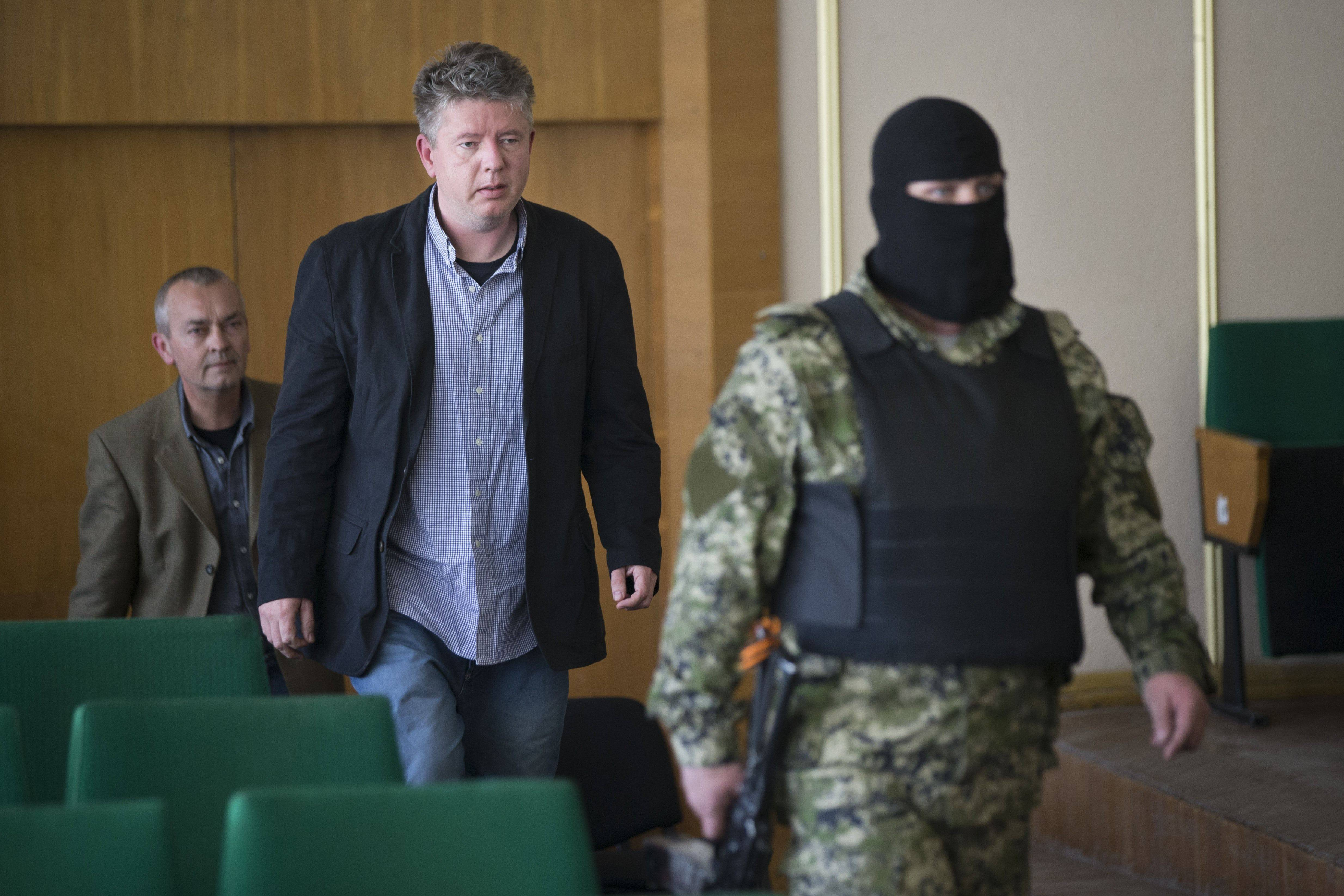 A pro-Russian gunman escorts a group of foreign military observers Sunday ahead of a news conference in Slovyansk, eastern Ukraine. As Western governments vowed to impose more sanctions against Russia and its supporters in eastern Ukraine, a group of foreign military observers remained in captivity Sunday accused of being NATO spies by a pro-Russian insurgency.