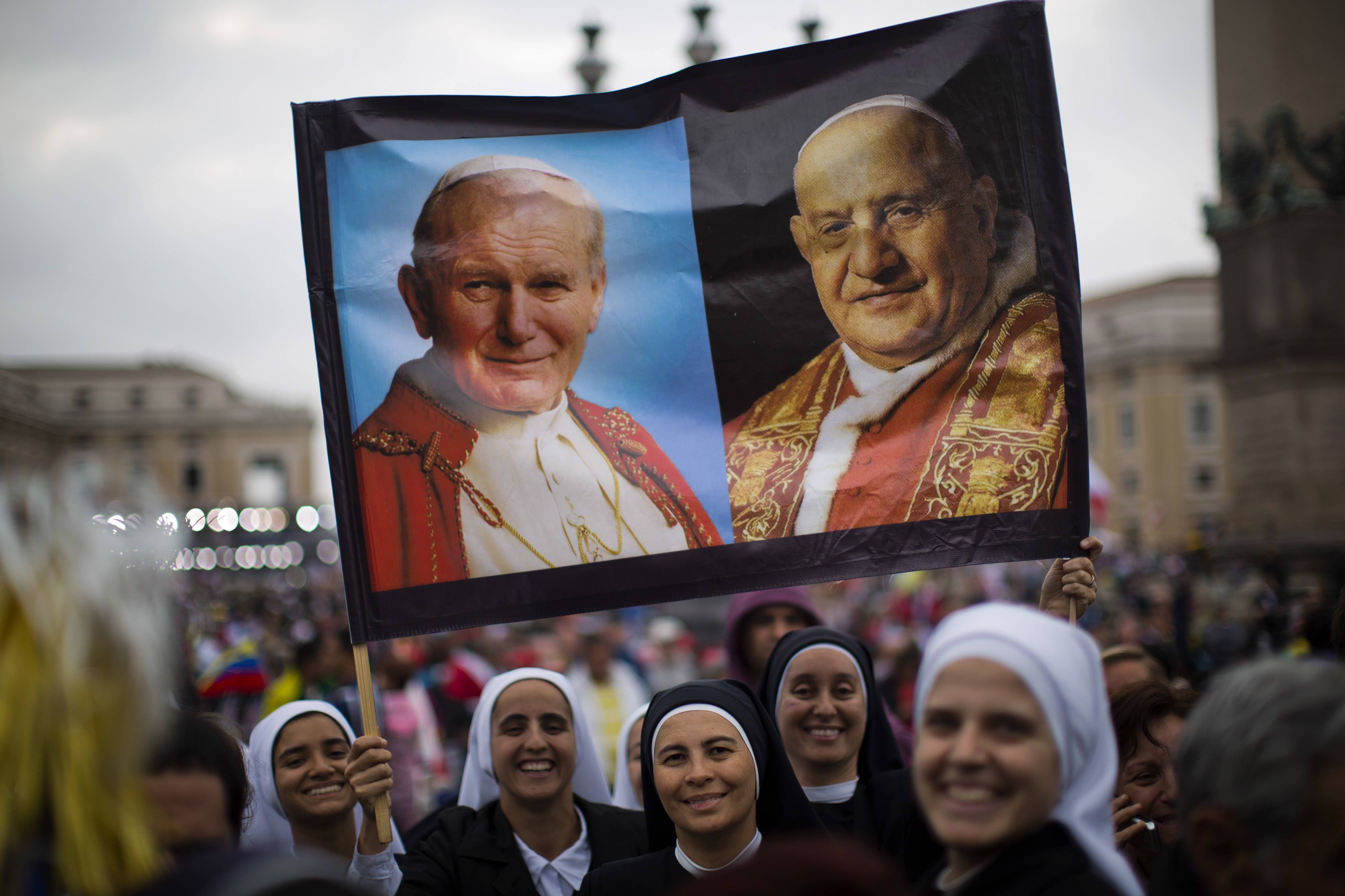 Nuns hold a poster with portraits of Pope John Paul II, left, and John XXIII, in St. Peter's Square at the Vatican Sunday. Pope Francis has declared his two predecessors John XXIII and John Paul II saints in an unprecedented canonization ceremony made even more historic by the presence of retired Pope Benedict XVI.