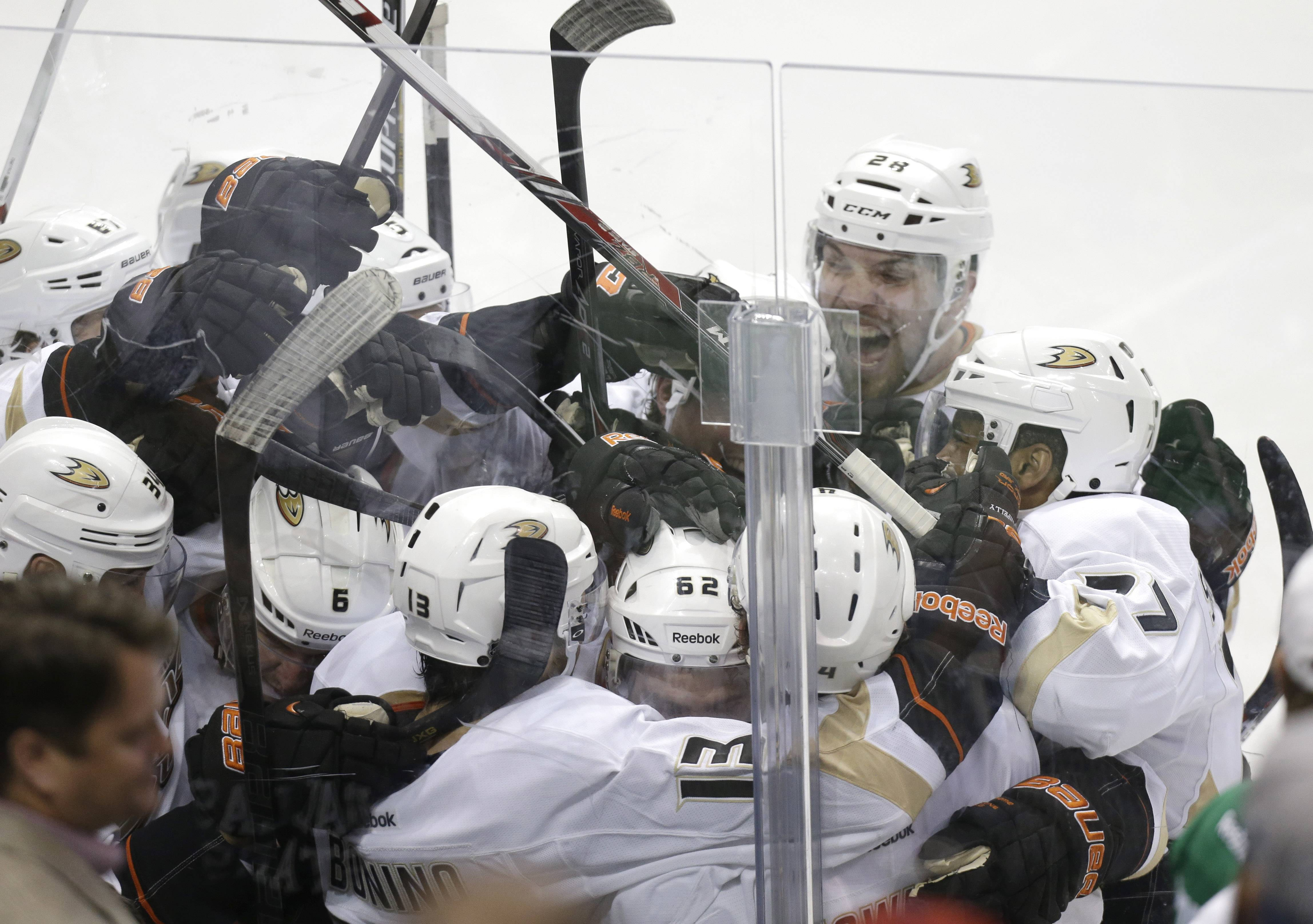 Anaheim Ducks Nick Bonino (13) is mobbed by his teammates after he scored the game winning goal in overtime of Game 6 to win the first-round NHL hockey playoff series against the Dallas Stars in Dallas, Sunday, April 27, 2014. The final score 5-4 for the Ducks.