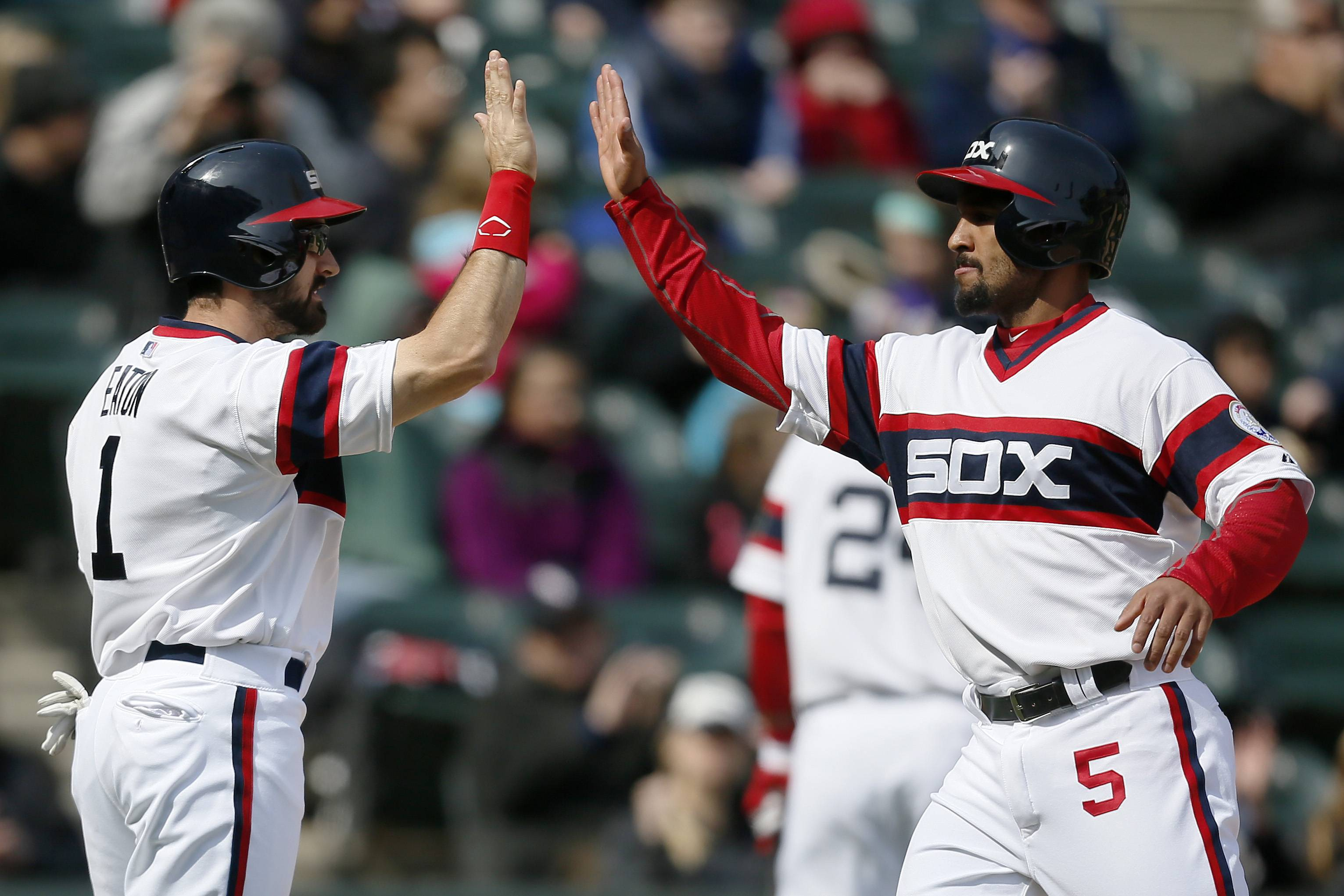 Chicago White Sox Adam Eaton, left, and Marcus Semien, right, high-five after scoring against the Tampa Bay Rays during the seventh inning of a baseball game, Sunday, April 27, 2014, in Chicago.