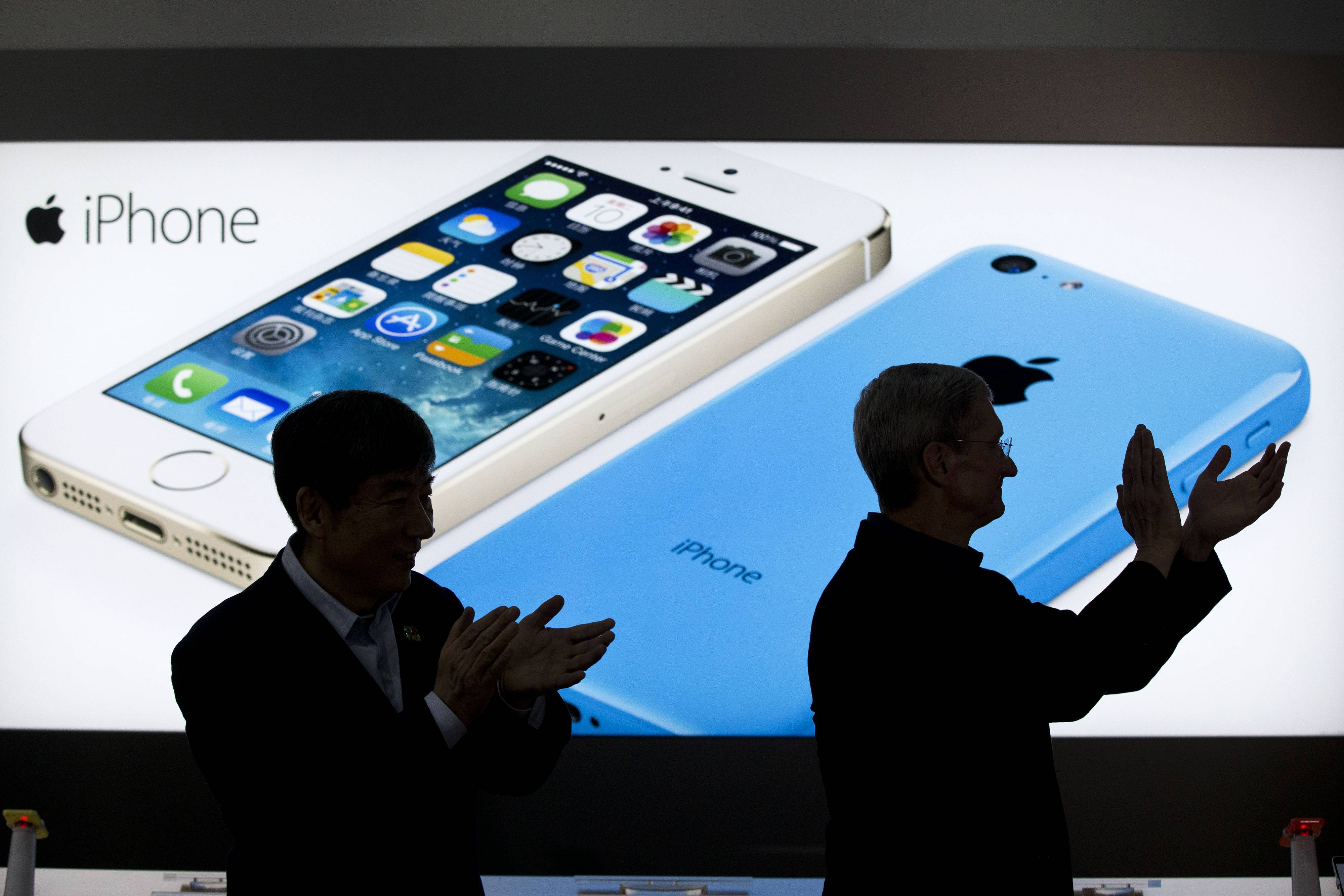 Apple CEO Tim Cook, right, and China Mobile's chairman Xi Guohua are silhouetted against a screen showing iPhone products as they applaud during a promotional event that marks the opening day of sales of China Mobile's 4G iPhone 5s and iPhone 5c at a shop of the world's largest mobile phone operator in Beijing, China. The high-stakes battle between the world's largest smartphone makers is scheduled to wrap up this week after a monthlong trial .