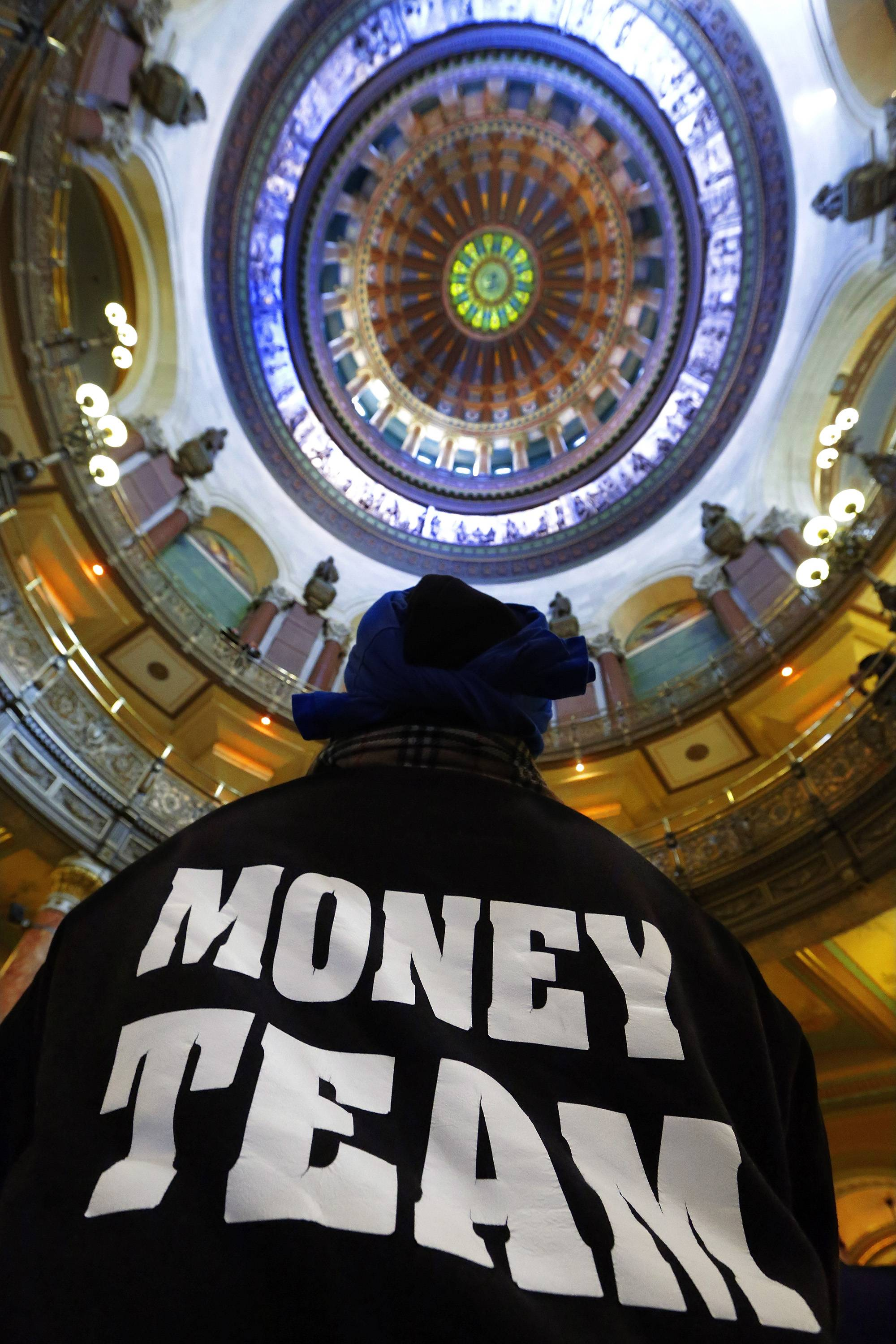 Timothy Russell, of Chicago, participates in a rally in support of raising the minimum wage in the rotunda of the Capitol in Springfield
