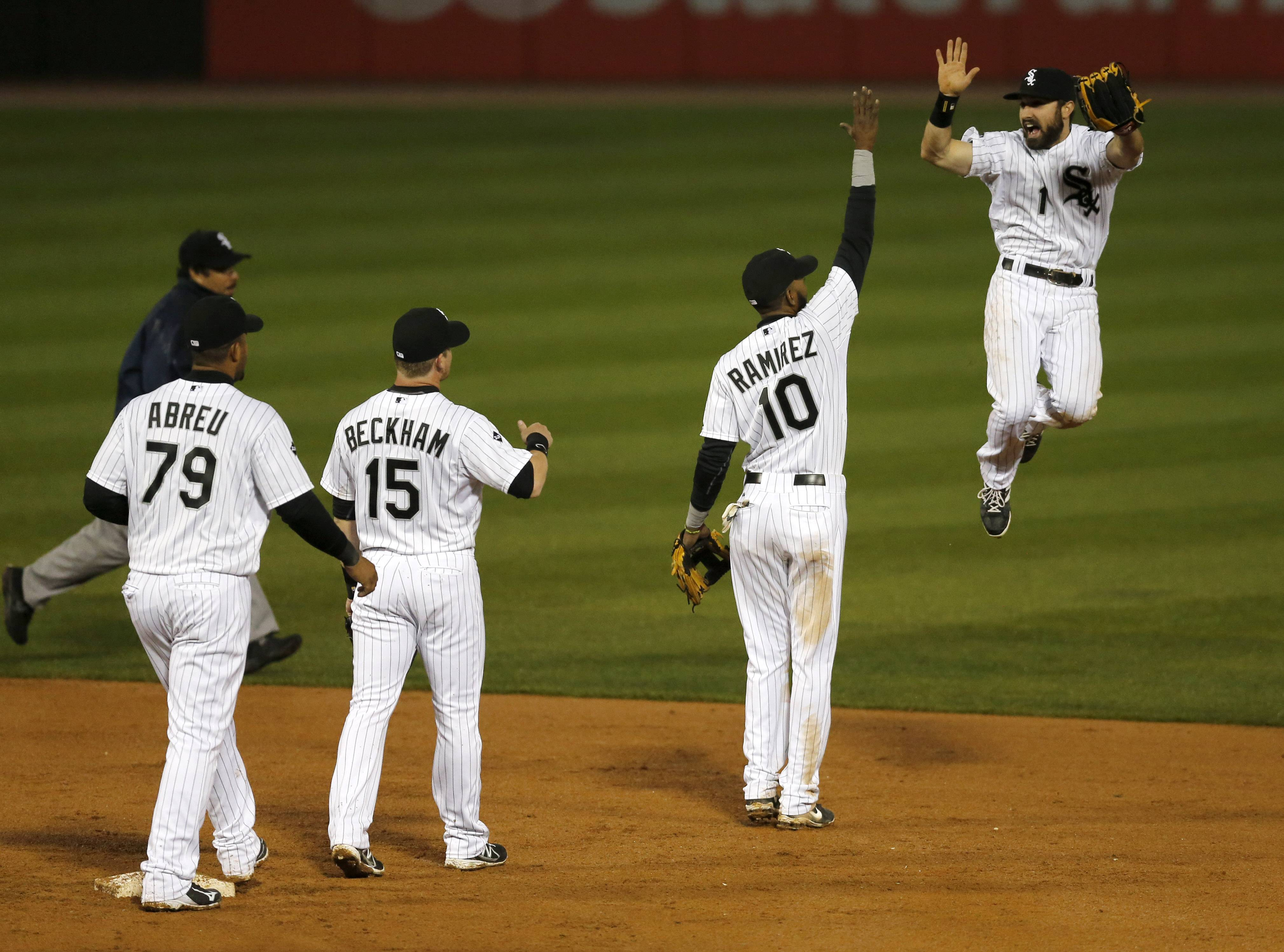Chicago White Sox shortstop Alexei Ramirez (10) celebrates with Adam Eaton (1) as teammates Jose Abreu (79) and Gordon Beckham (15) watch after the White Sox's 7-3 win over the Tampa Bay Rays.