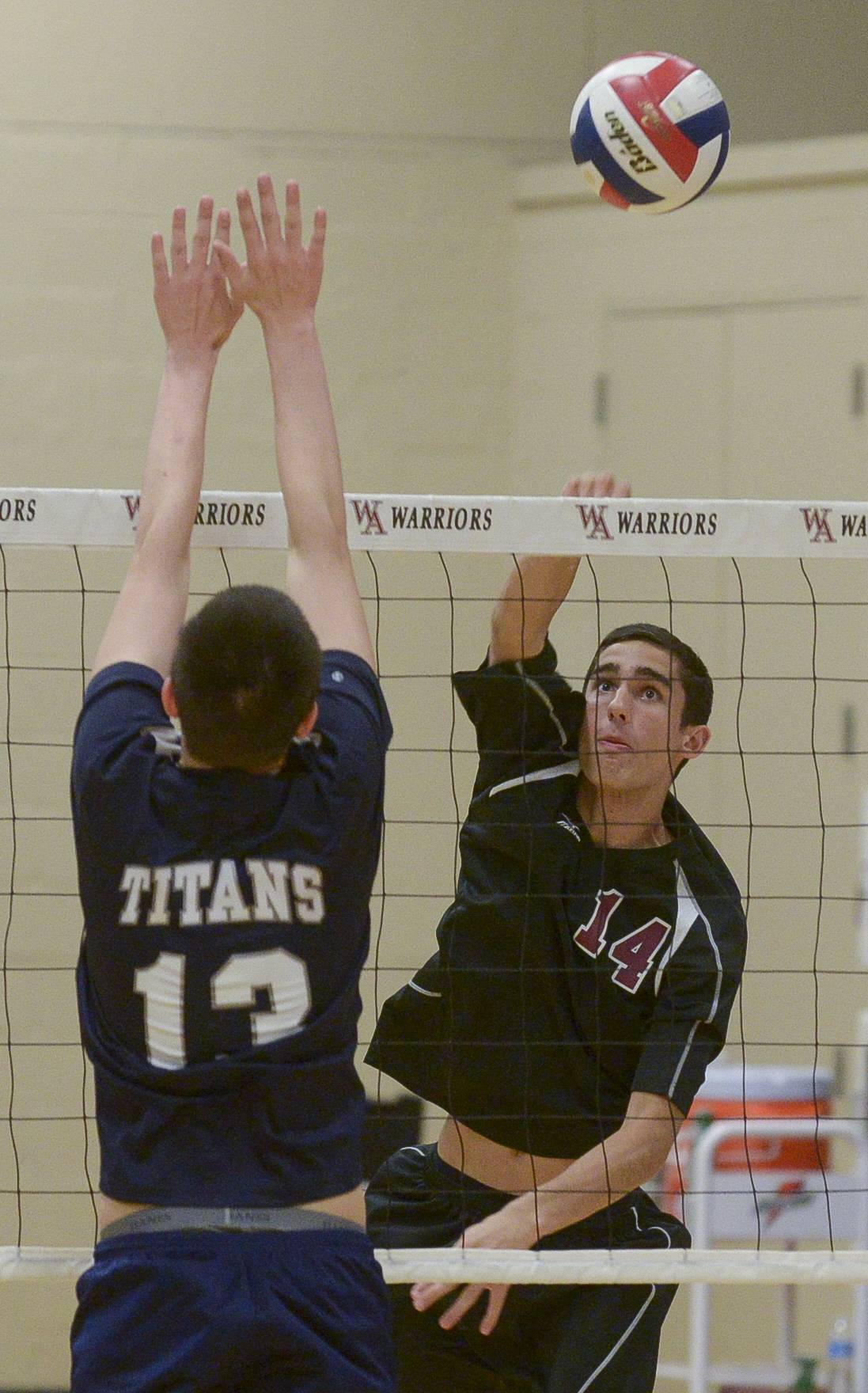 Wheaton Academy's Braden Martin fires one past IMSA's Aaron Victor during boys volleyball in West Chicago Monday.