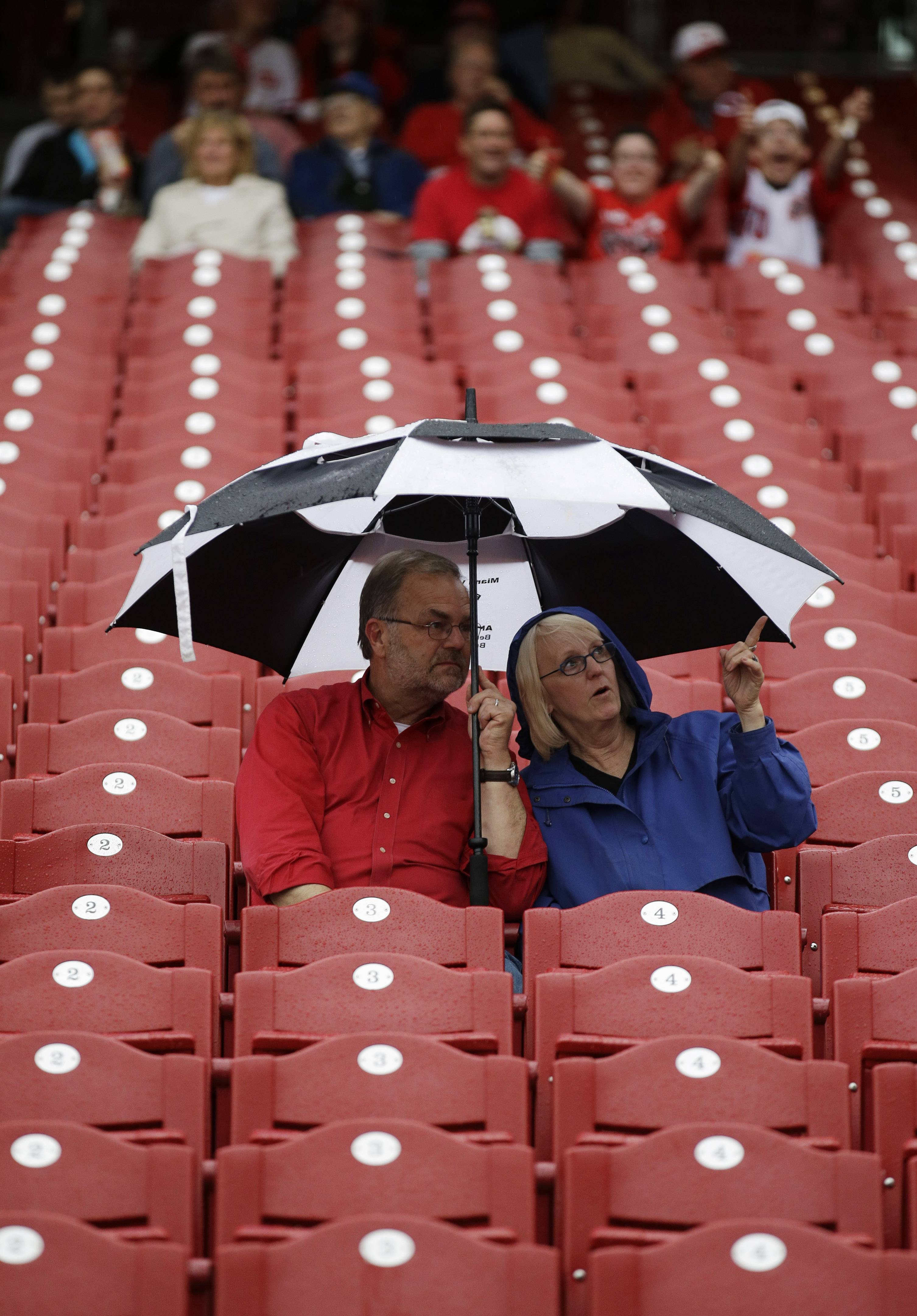 Fans sit in the stands before a baseball game between the Cincinnati Reds and the Chicago Cubs that was delayed by rain.