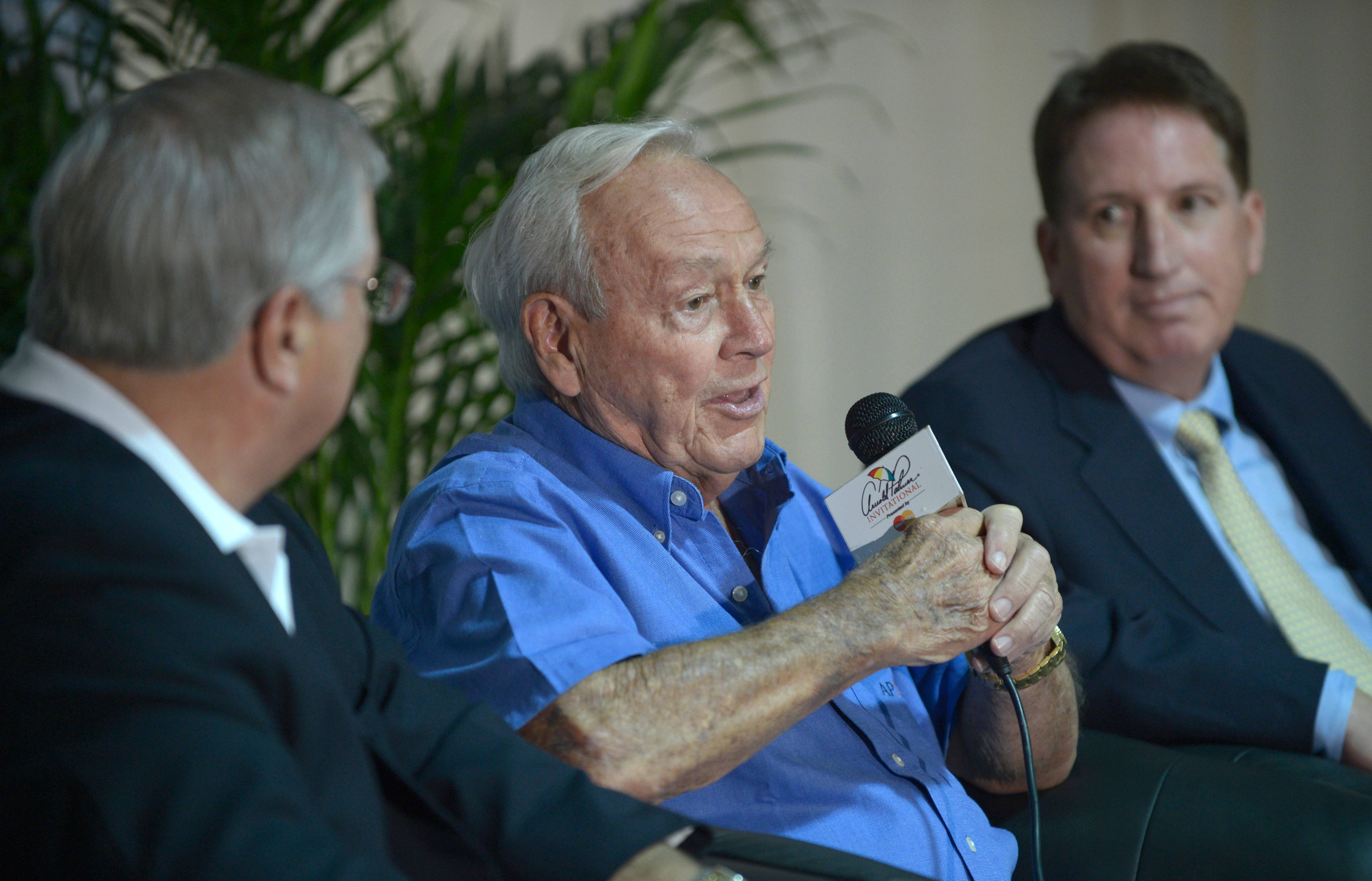 PNC Financial Services Group Chairman & CEO James Rohr, left, and Champions Tour President Mike Stevens, right, listen as Arnold Palmer speaks during a news conference in 2012.