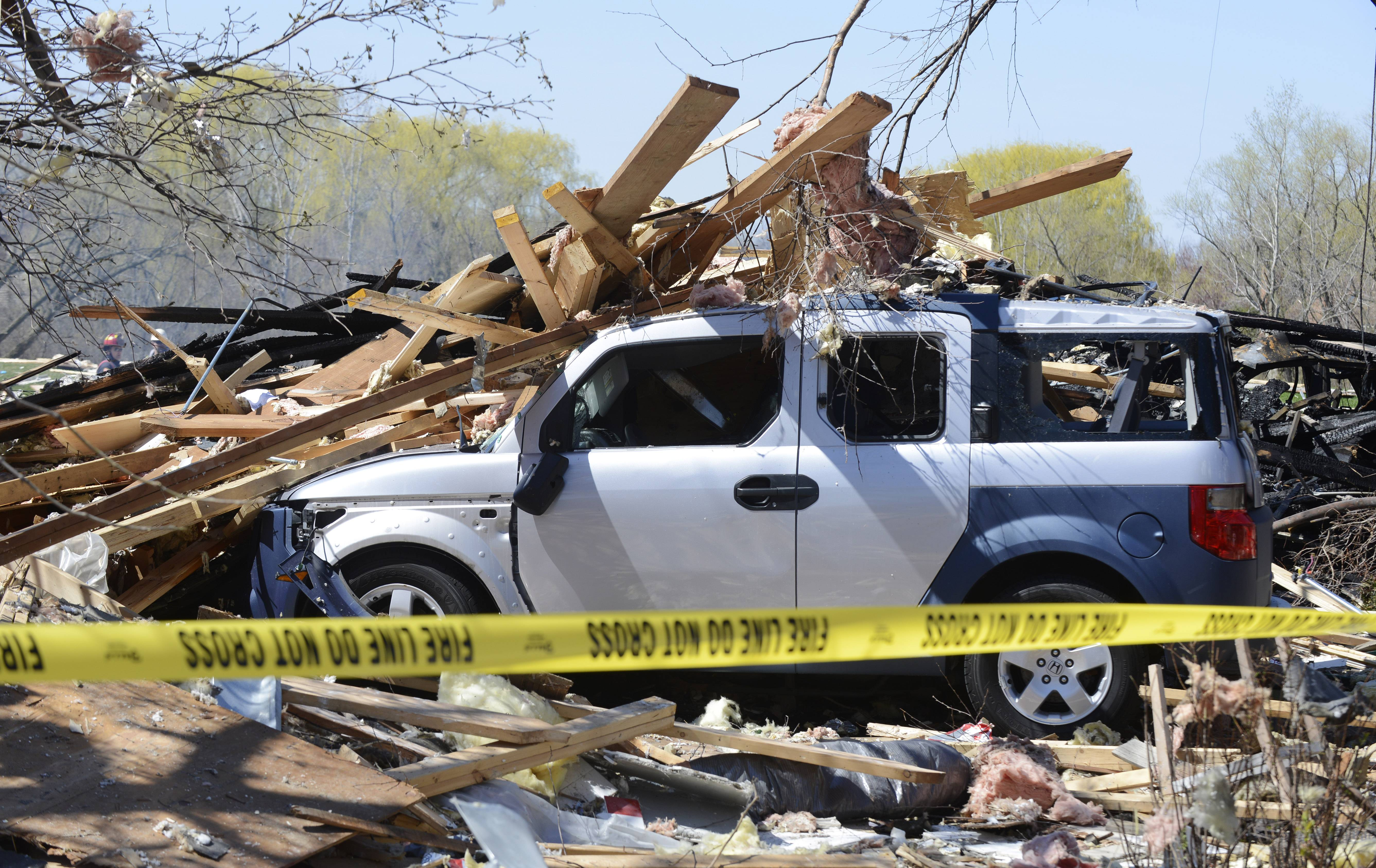 A car is littered with debris after the an explosion Friday night leveled a home in Long Grove. Investigators remained on the scene of the blast Monday, though they admit that the extent of the damage may keep them from discovering its exact cause.