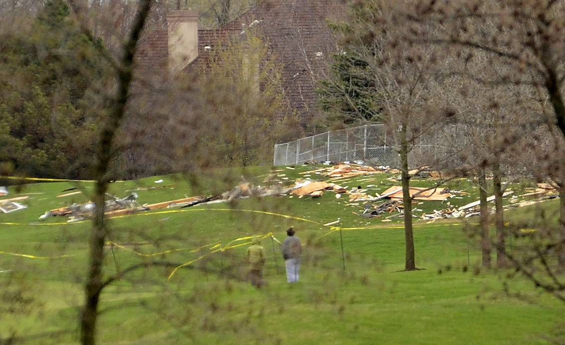 Bystanders on the Royal Melbourne Country Club view the wreckage from Friday night's explosion on Trenton Court in Long Grove. Investigators continue to sift through the wreckage in hopes of finding clues to the cause of the blast.