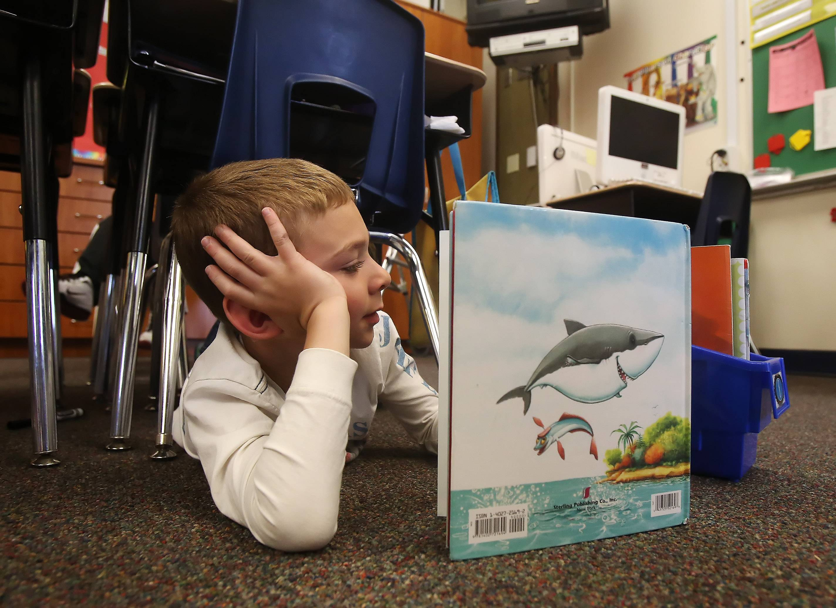 First grader Jackson Groth lies under a desk Monday as he reads in Amy Reichert's class while classmates recline on the floor, sit in a big chair and hide under desks during reading time at Butterfield School in Libertyville.